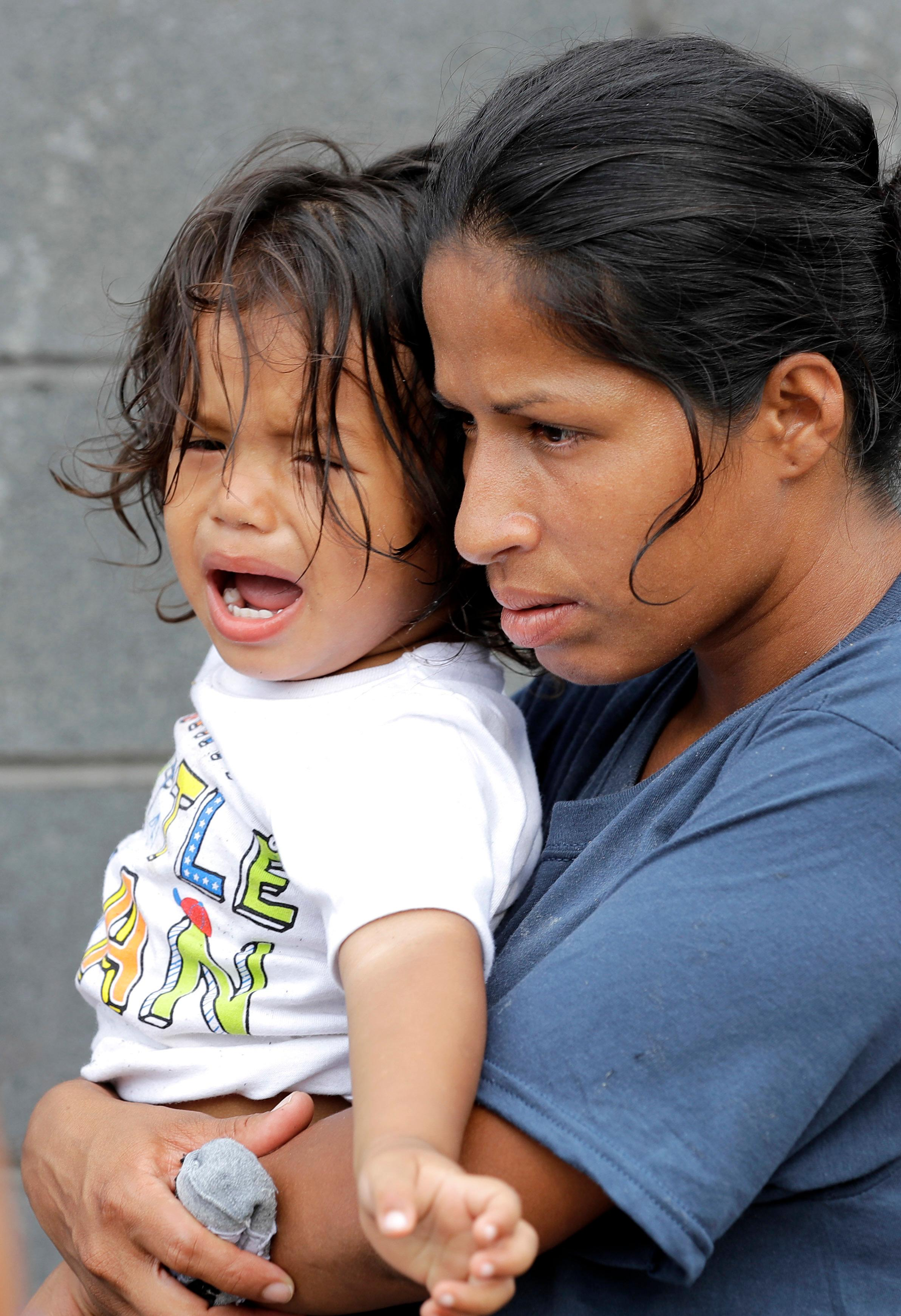 Jesus Funes, 19-months, cries as his mother, Diva Funes, both immigrants from Honduras, holds him after being escorted back to Reynosa, Mexico, Thursday, June 21, 2018. The family, who was seeking asylum, said they were told by officials they would be separated so they voluntarily returned to Mexico. (AP Photo/David J. Phillip)