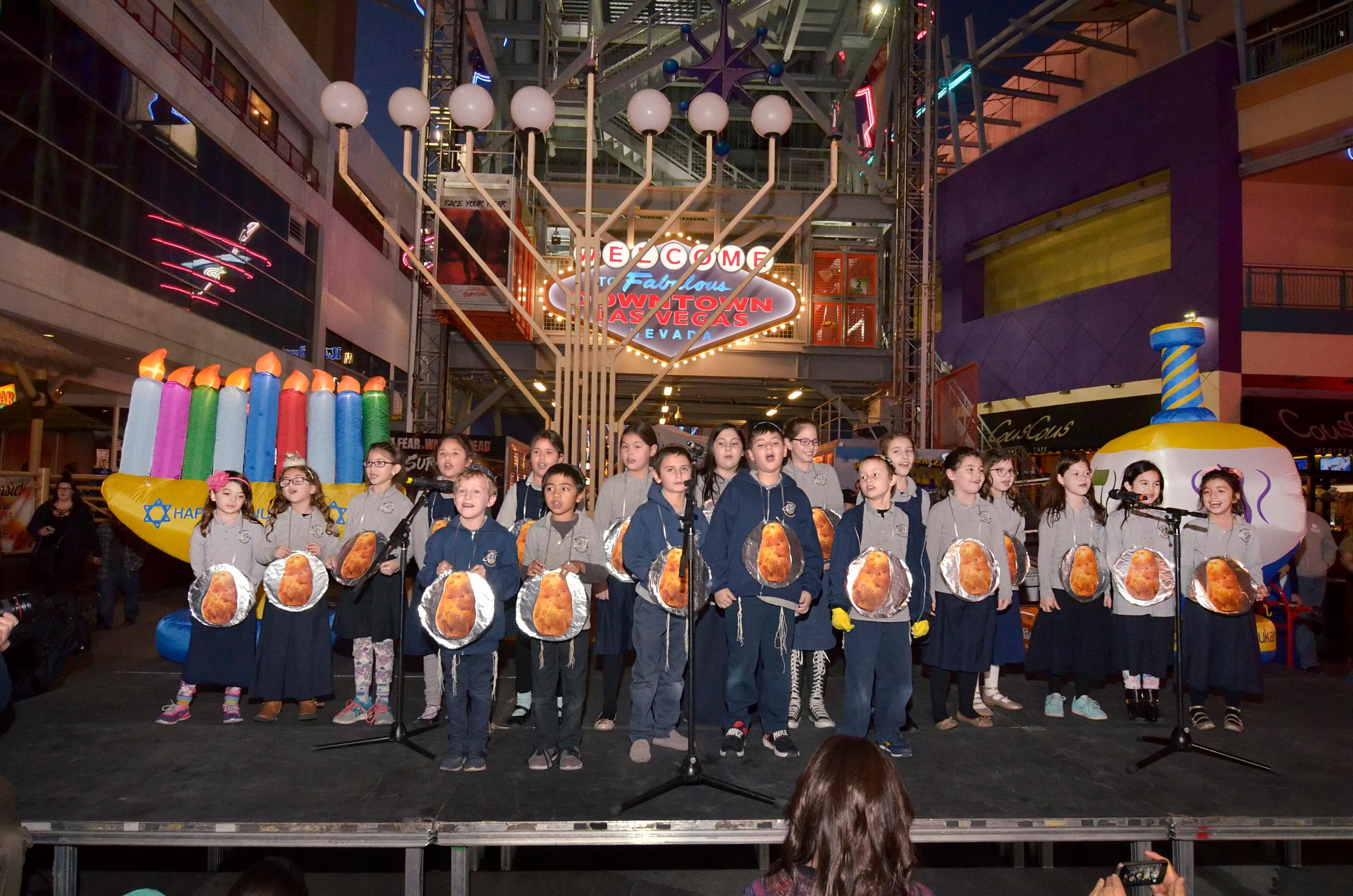 The Desert Torah Academy Childrens Choir performs during a menorah lighting ceremony. Rabbi Shea Harlig, of the Chabad Jewish Center of Southern Nevada, Las Vegas Mayor Carolyn Goodman, Jonathan Jossel, CEO of the Plaza hotel-casino, and Patrick Hughes, President and CEO of Fremont Street Experience, were on hand for the first night of Hanukkah which was marked with the lighting of a 20-foot Grand Menorah on Fremont Street in downtown Las Vegas on Tuesday, Dec. 12, 2017. CREDIT: Bill Hughes/Las Vegas News Bureau