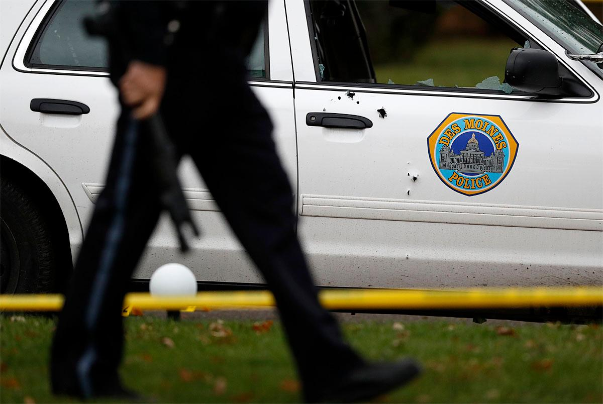 Bullet holes are seen on the side of a Des Moines police department squad car at the scene of a shooting, Wednesday, Nov. 2, 2016, in Des Moines, Iowa. Authorities apprehended a man Wednesday suspected in the early morning killings of two Des Moines area police officers who were shot to death while sitting in their patrol cars in what authorities described as separate ambush-style attacks. (AP Photo/Charlie Neibergall)
