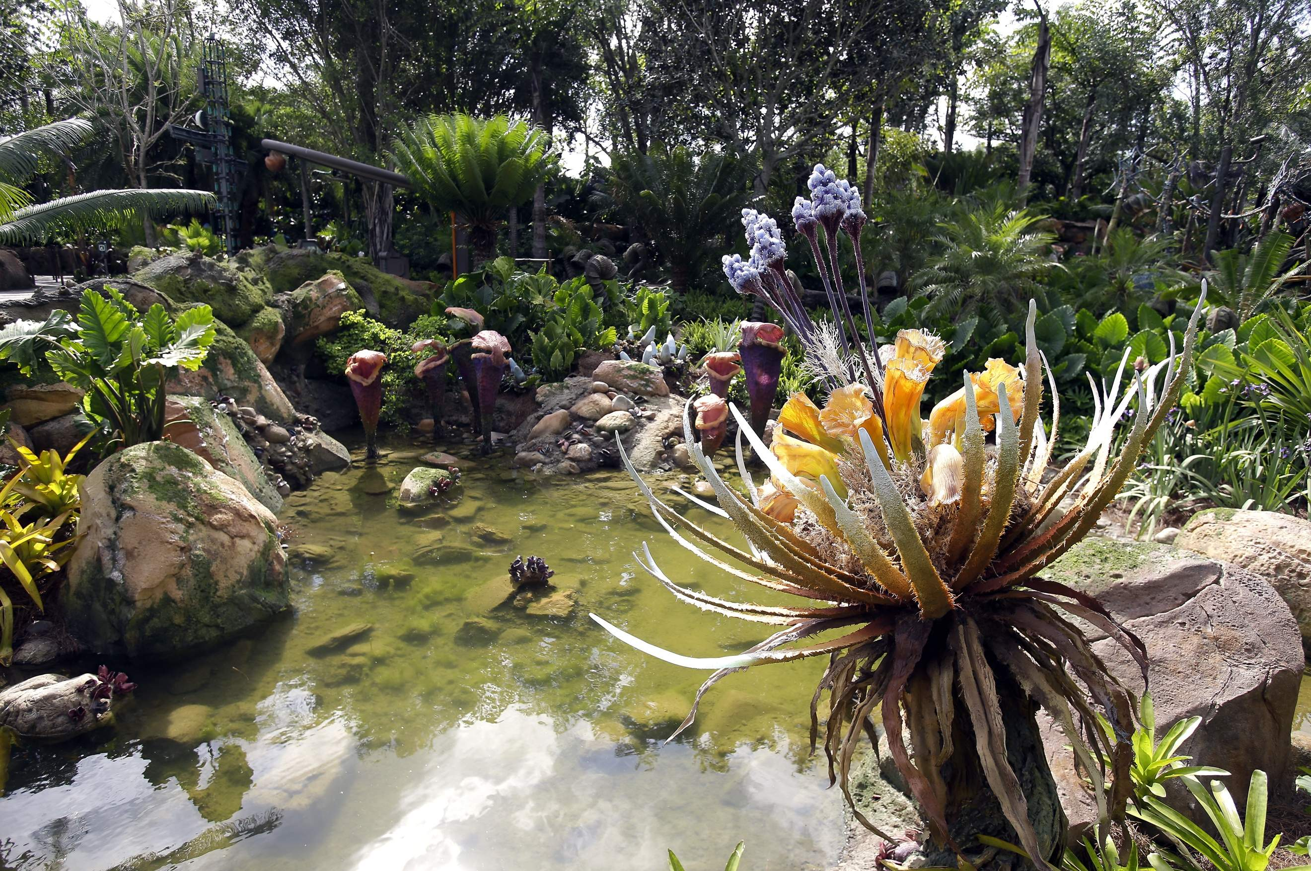 In this Saturday, April 29, 2017, photo, landscaping consisting of real Earth plant species mixed with sculpted Pandora flora surrounds a pond at the Pandora-World of Avatar land attraction in Disney's Animal Kingdom theme park at Walt Disney World in Lake Buena Vista, Fla. The 12-acre land, inspired by the 'Avatar' movie, opens in Florida at the end of May at Walt Disney World's Animal Kingdom. It cost a half-billion dollars. THE ASSOCIATED PRESS