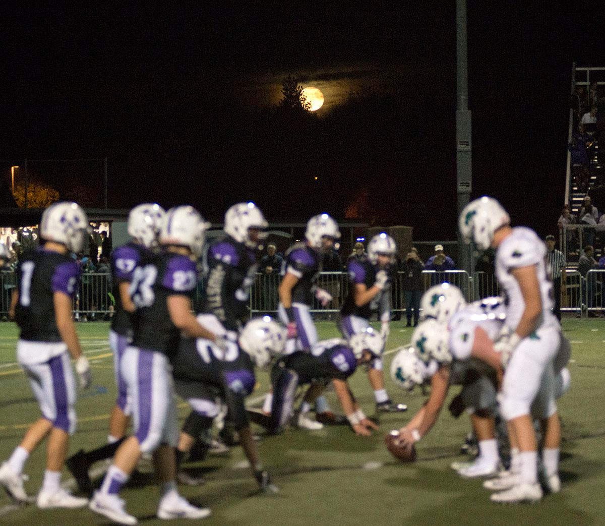 South Eugene Axemen players and Sheldon Irish players gather at the line of scrimmage under the harvest moon. Sheldon Irish defeated South Eugene Axemen 63-6 on Friday night at South Eugene Highschool in Eugene, Ore. Photo by Rhianna Gelhart, Oregon News Lab