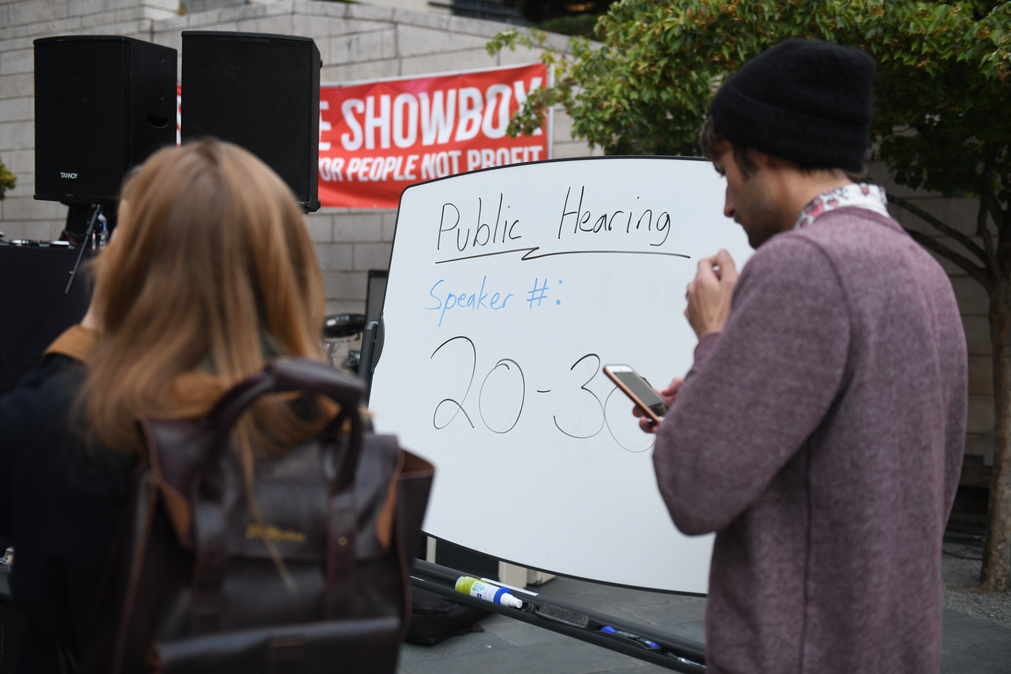 "Tonight (September 19, 2018) marked the first public hearing regarding The Showbox Seattle, an iconic venue that is facing demolition for a luxury high rise, despite public outcry. Before the meeting, a rally was held outside city hall where musicians, fans and members of the public gathered to ""Save the Showbox"" and support efforts to preserve the beloved space. A packed public hearing followed the free concert - no decisions expected out of this meeting, just city leaders getting feedback on whether to make a permanent extension of the Pike Place Historic District to include the Showbox. (Image: Chona Kasinger / Seattle Refined)"