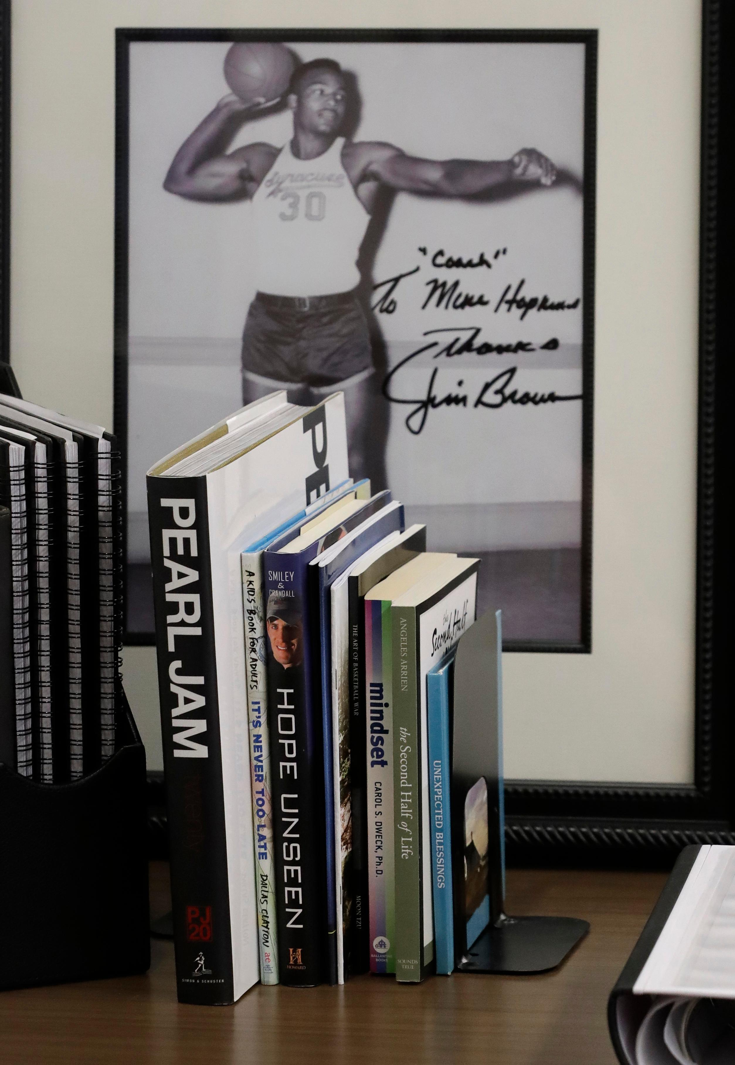 In this Sunday, Jan. 28, 2018 photo, a desk in the office of Washington head coach Mike Hopkins, in Seattle, displays books and an autographed photo of basketball legend Jim Brown during his playing days at Syracuse University, where Hopkins was a longtime assistant coach before taking over at Washington at the start of the 2018 season. One of the most surprising stories in college basketball is what Hopkins is doing in his first season at Washington and how the Huskies are in the conversation for an NCAA bid entering February. Hopkins is also a big fan of the Seattle-based band Pearl Jam. (AP Photo/Ted S. Warren)