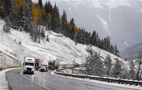 Trucks ascend Vail Pass along I-70 after overnight snow fell in the mountains of Colorado.