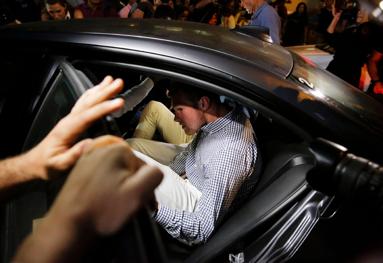 American Olympic swimmer Jack Conger gets into a car as he and fellow swimmer Gunnar Bentz leave a police station in the Leblon neighborhood of Rio de Janeiro, Brazil, Thursday, Aug. 18, 2016. The two were taken off their flight from Brazil to the U.S. on Wednesday by local authorities amid an investigation into a reported robbery targeting swimmer Ryan Lochte and his teammates. A Brazilian police officer told The Associated Press that Lochte fabricated a story about being robbed at gunpoint in Rio de Janeiro. (AP Photo/Leo Correa)