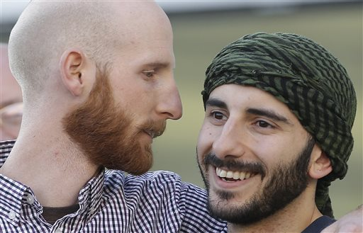 "Plaintiffs Derek Kitchen, left, and Moudi Sbeity stand together during the Utah Unites for Marriage ""send-off"" event in Salt Lake City."