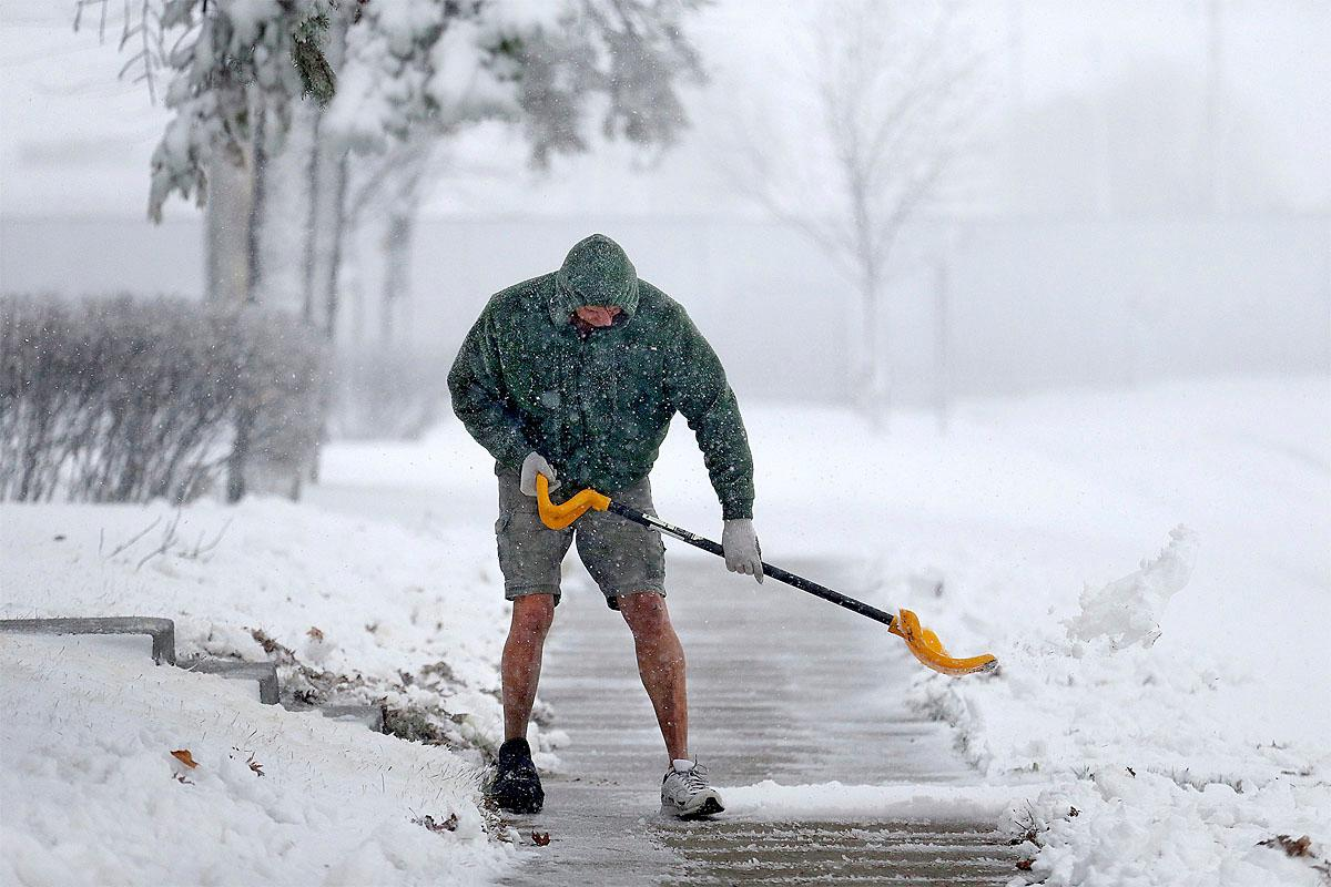 Peter Lidstone shovels his sidewalk during a snow storm,  Friday, Nov. 18, 2016 in St. Cloud, Minn.  The National Weather Service has issued a blizzard warning for Friday in eastern parts of North and South Dakota and Minnesota, as well as winter storm warnings for other parts of those states and Nebraska.    ( Elizabeth Flores/Star Tribune via AP)