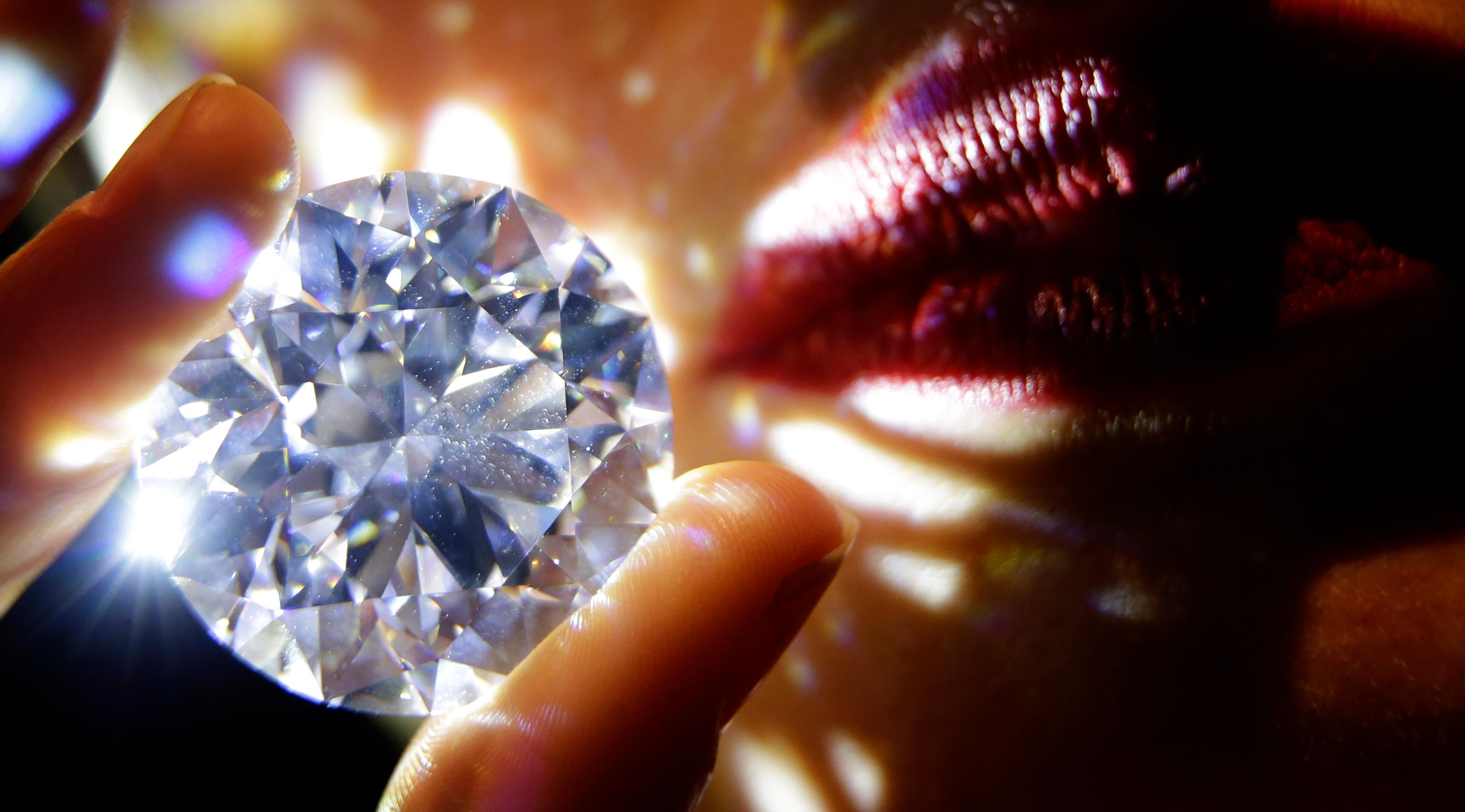 A 102.34, carat, D colour and flawless white diamond held by a model is displayed at Sotheby's auction house in London, Thursday, Feb. 8, 2018. The diamond is the world largest known round