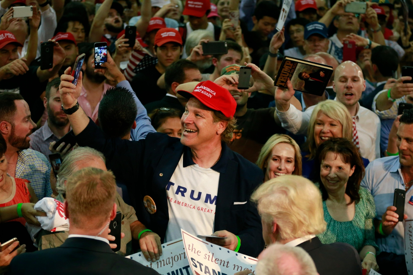 A man takes a selfie while getting his sign autographed by Republican presidential candidate Donald Trump during a rally, Thursday, June 2, 2016, in San Jose, Calif. (AP Photo/Jae C. Hong)