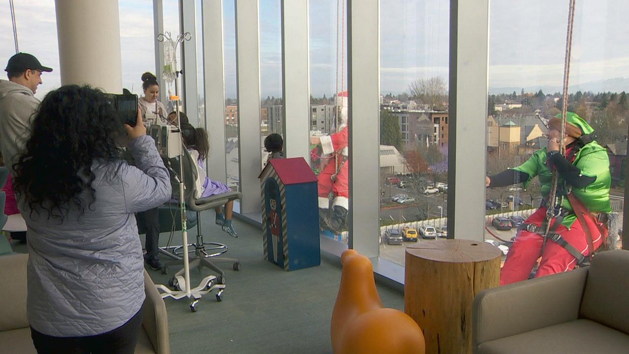 Santa and his friends bring some holiday cheer to children at Randall Children's Hospital in North Portland on Tuesday as they clean the building's windows. (KATU Photo)