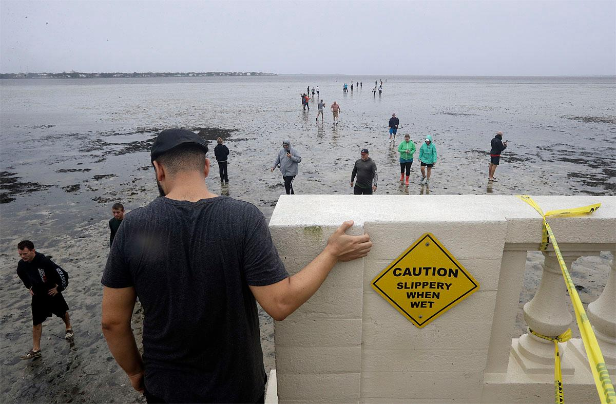 People walk out onto what is normally four feet of water in Old Tampa Bay, Sunday, Sept. 10, 2017, in Tampa, Fla. Hurricane Irma and an unusual low tide pushed water out over 100 yards. (AP Photo/Chris O'Meara)