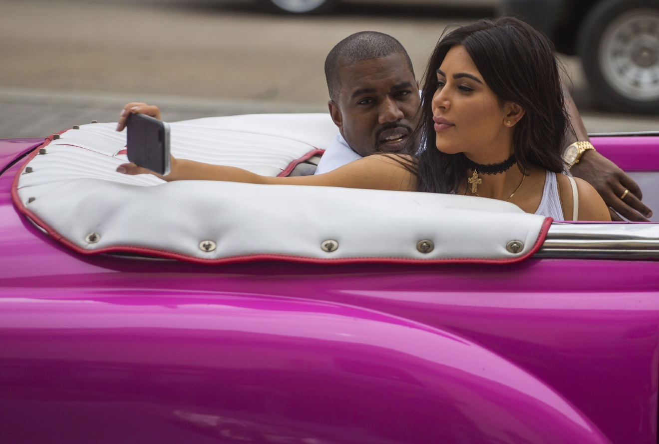 American reality-show star Kim Kardashian takes a selfie as she rides on a classic car next to her husband, rap superstar Kayne West in Havana, Cuba, Wednesday, May 4, 2016. West, Kardashian and members of her reality-show-star family have become the latest celebrities to visit Havana. They visited HavanaÂ?s Museum of Rum Wednesday, stepping out of a hot-pink antique American convertible as they snapped selfies and were recorded by a television crew following them around.(AP Photo/Desmond Boylan)