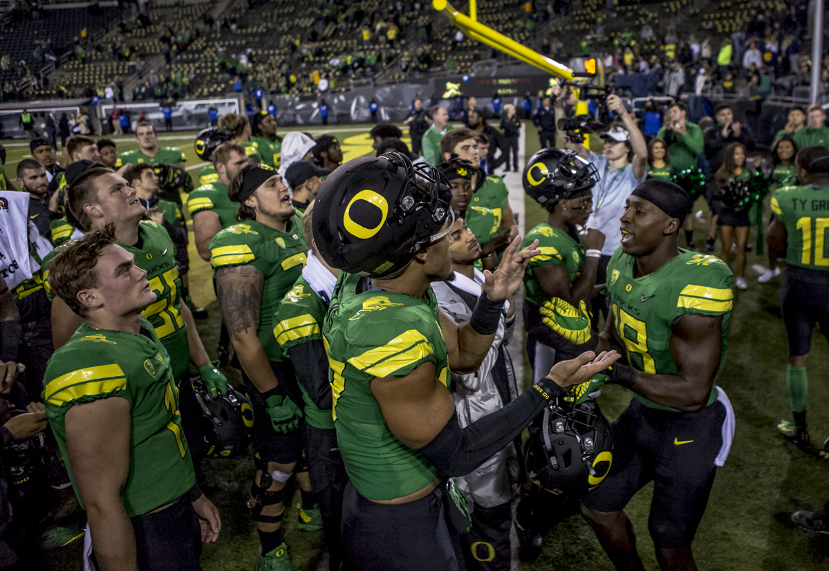 Oregon players celebrate their win following a game against California. The Oregon Ducks defeated the California Golden Bears 45 to 24 during an evening game on Saturday September 30, 2017. Photo by Ben Lonergan, Oregon News Lab