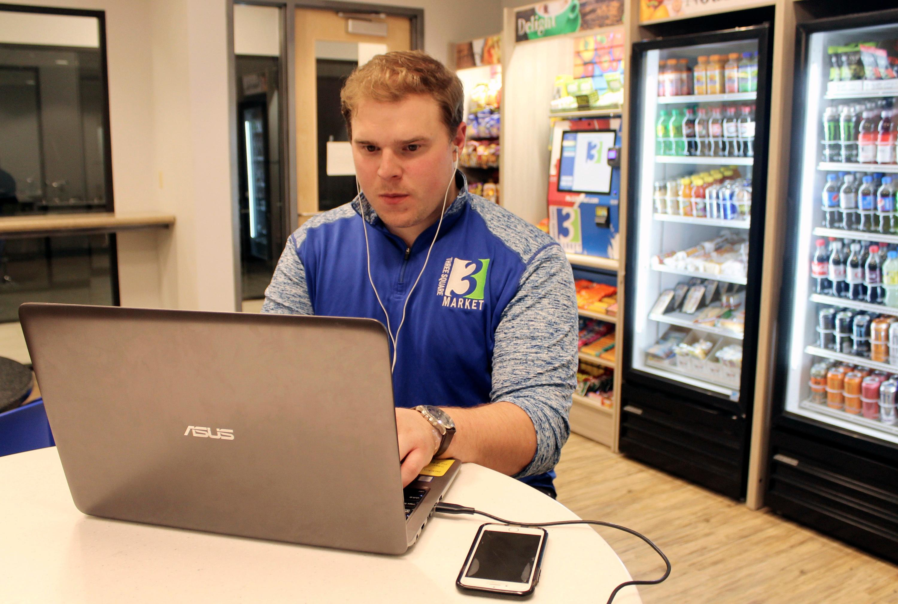Tony Danna, vice president of international development at Three Square Market, works on his laptop in a company break room at its headquarters, Tuesday, July 25, 2017 in River Falls, Wis. The software company is offering to microchip its employees, enabling them to open doors, log onto their computers and purchase break room snacks with a simple wave of the hand. (AP Photo/Jeff Baenen)
