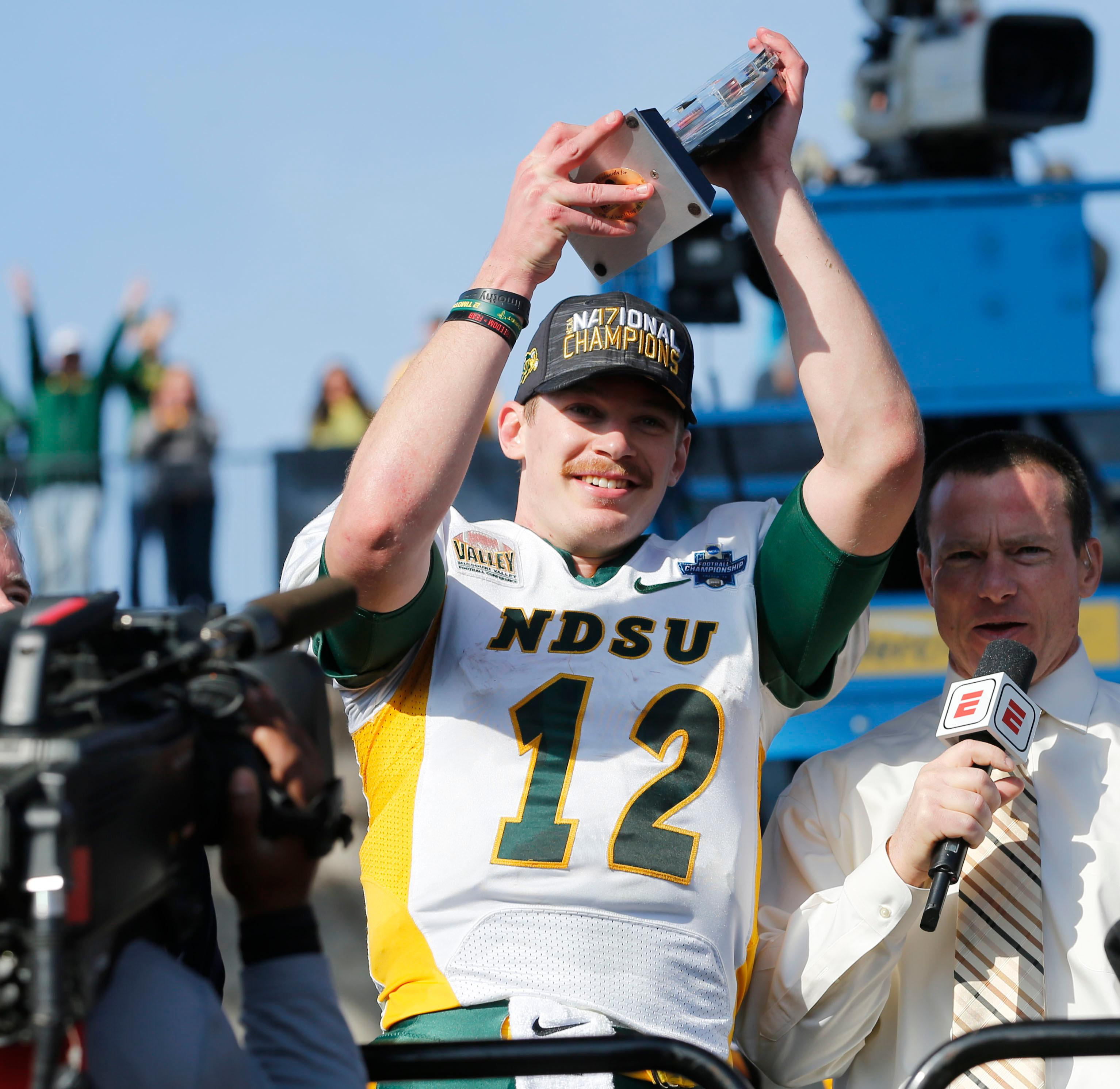 North Dakota State quarterback Easton Stick (12) hoists up the Most Outstanding Player award after the team defeated James Madison 17-13 in the FCS championship NCAA college football game at Toyota Stadium in Frisco, Texas, Saturday, Jan. 6, 2017. (Vernon Bryant/The Dallas Morning News via AP)