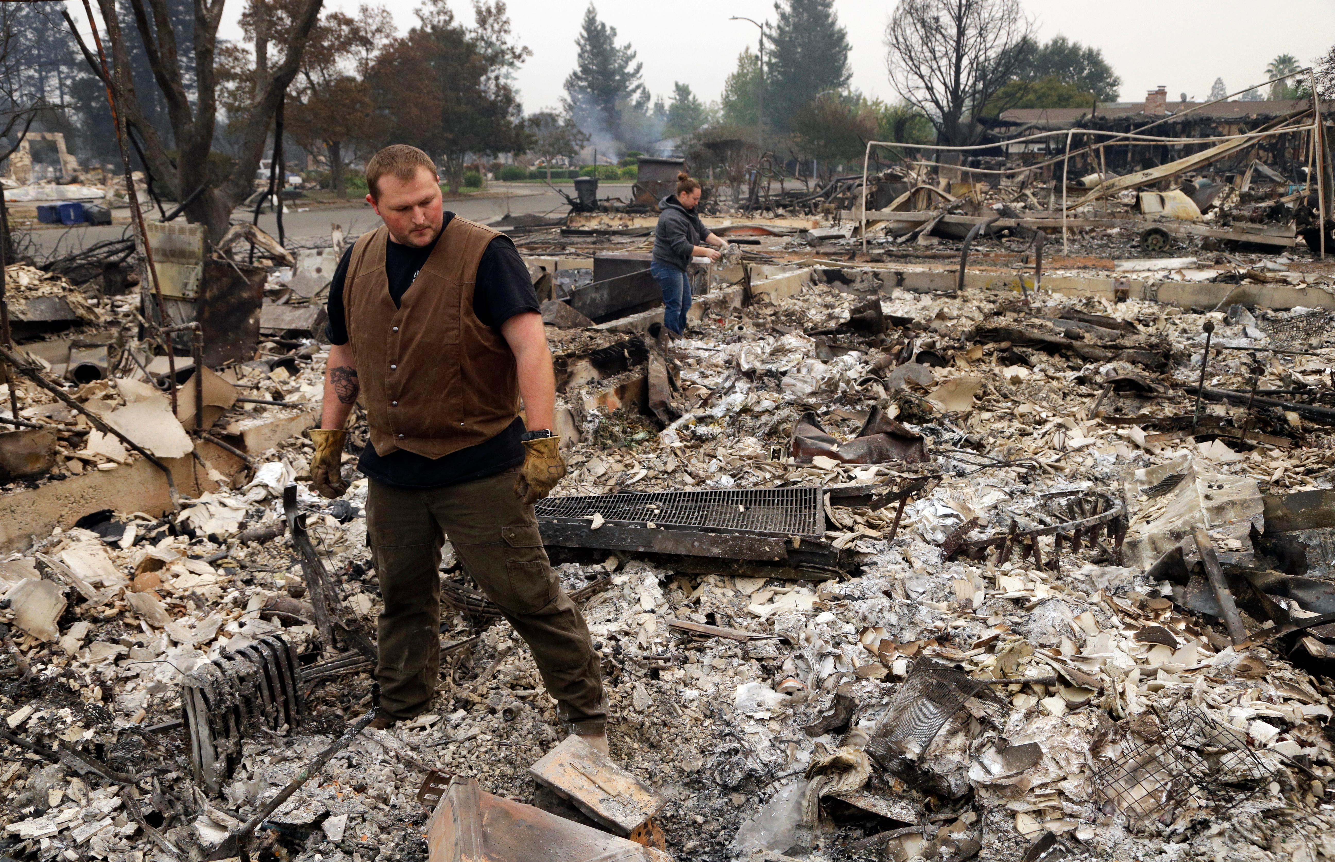 Luke Baier, left, and his wife Gina Baier look through the remains of their home in the Coffey Park area of Santa Rosa, Calif., on Tuesday, Oct. 10, 2017. An onslaught of wildfires across a wide swath of Northern California broke out almost simultaneously then grew exponentially, swallowing up properties from wineries to trailer parks and tearing through both tiny rural towns and urban subdivisions. (AP Photo/Ben Margot)