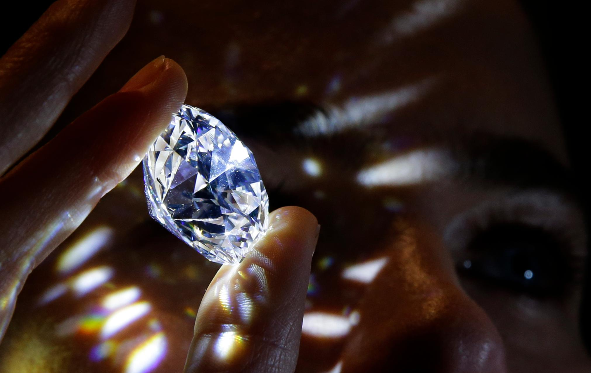 "A 102.34, carat, D colour and flawless white diamond held by a model is displayed at Sotheby's auction house in London, Thursday, Feb. 8, 2018. The diamond is the world largest known round brilliant diamond to have achieved ""perfection in all critical criteria - Colour, Clarity, Cut and Carat"", and is expected to reach considerably over 33.7 million dollars by private sale in London. (AP Photo/Alastair Grant)"