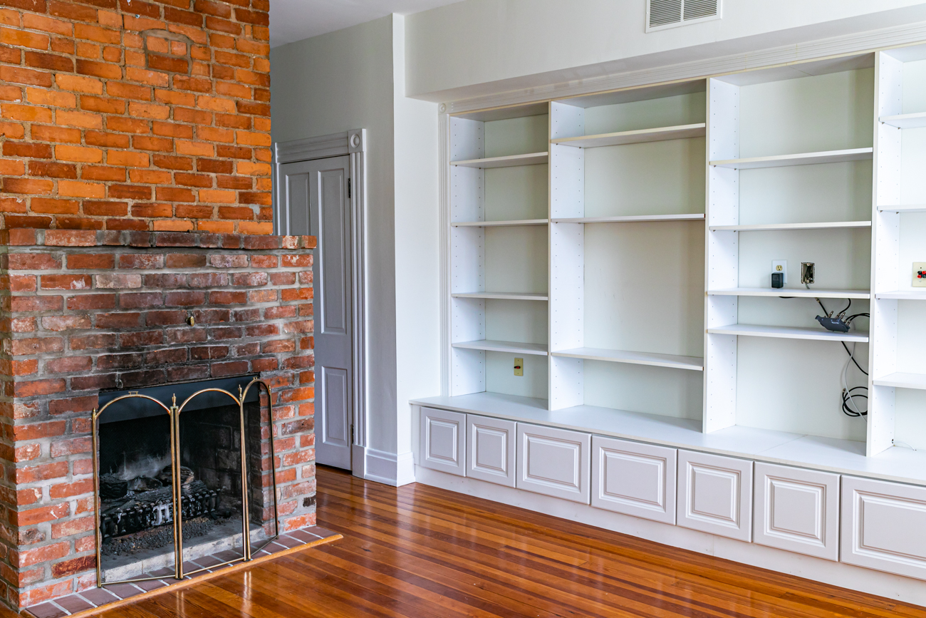 The living area includes plenty of built-in bookshelves and a great media area. The fireplace is original, too, but upgraded to gas for convenience. / Image: Amy Spasoff // Published: 5.22.19