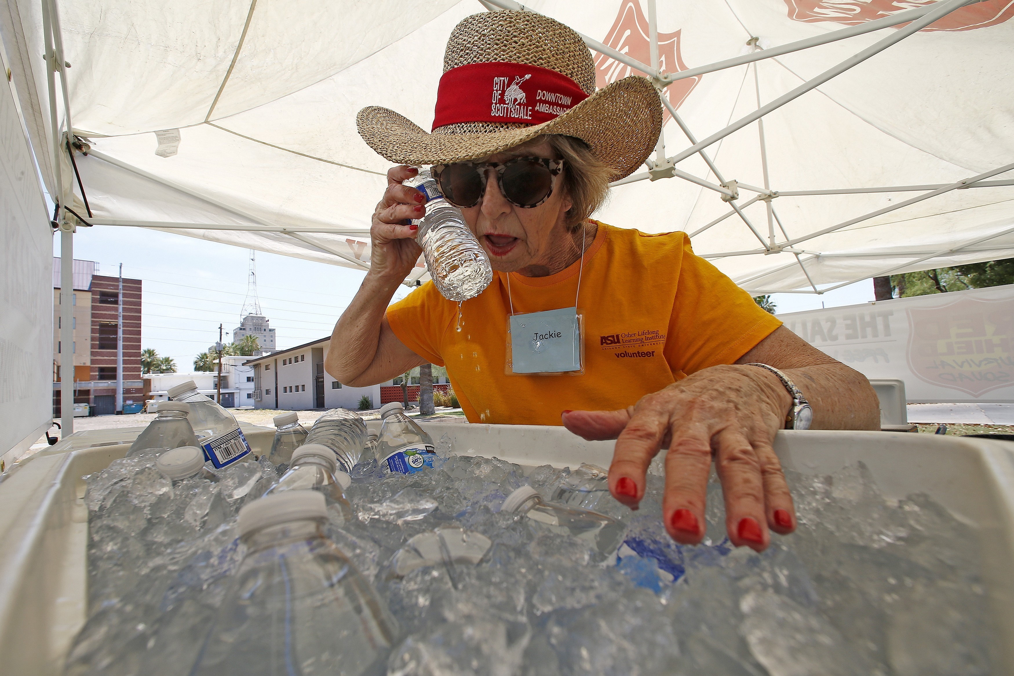 Salvation Army volunteer Jackie Rifkin tries to keep cool at she works at a special Salvation Army hydration station to help people try to keep hydrated and stay cool as temperatures climb to near-record highs, Monday, June 19, 2017, in Phoenix. (AP Photo/Ross D. Franklin)