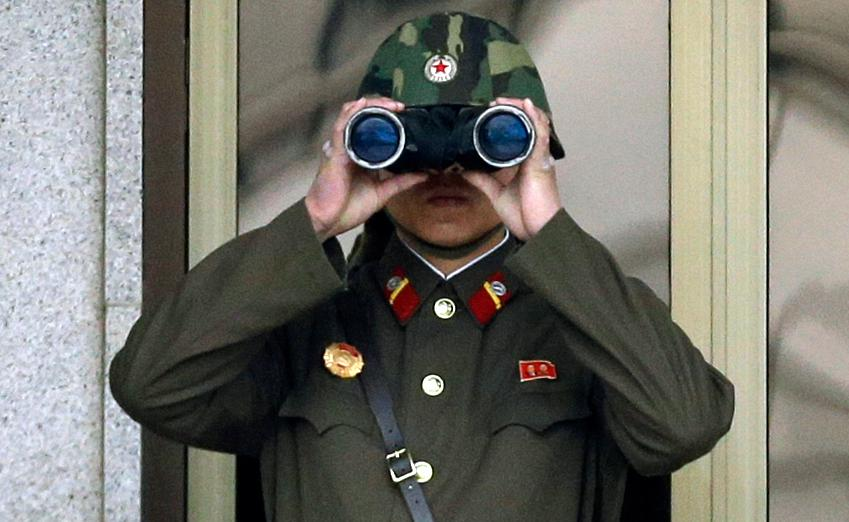 In this Tuesday, April 23, 2013, file photo, a North Korean soldier looks at the southern side through a pair of binoculars at the border village of Panmunjom, which has separated the two Koreas since the Korean War, in Paju, north of Seoul, South Korea. Threatening to fire a volley of missiles toward a major U.S. military hub _ and the home to 160,000 American civilians _ may seem like a pretty bad move for a country that is seriously outgunned and has an awful lot to lose. But pushing the envelope, or just threatening to do so, is what North Korea does best. (AP Photo/Lee Jin-man, File)