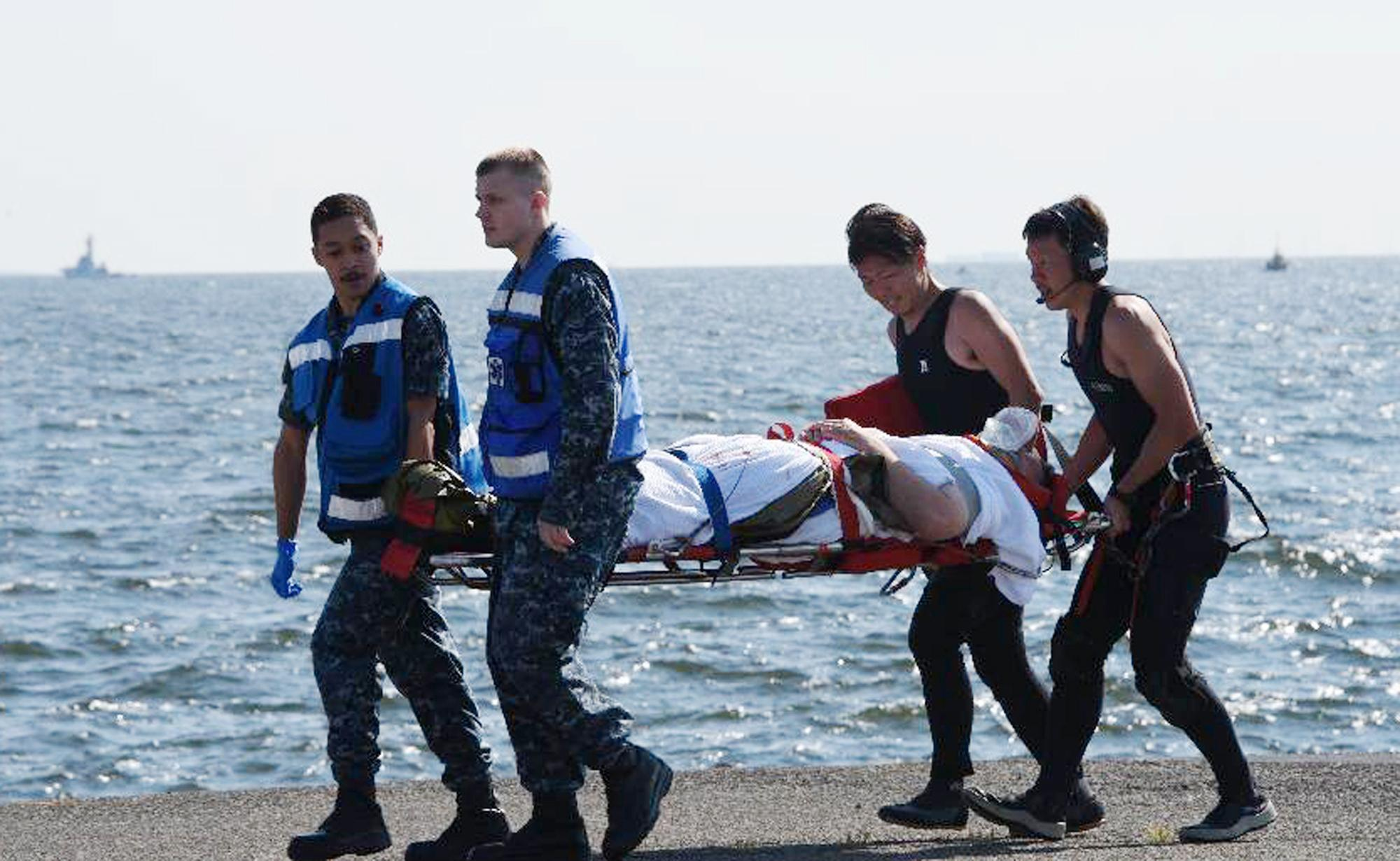 In this photo released by Japan's Defense Ministry, an injured USS Fitzgerald personnel is carried by U.S. military personnel, left, and Japanese Maritime Self-Defense Force members upon arriving to the U.S. Naval base in Yokosuka, southwest of Tokyo, after the U.S. destroyer collided with the Philippine-registered container ship ACX Crystal in the waters off the Izu Peninsula Saturday, June 17, 2017. Seven Navy sailors were missing and at least two, including the captain, were injured after the collision off the coast of Japan before dawn Saturday, the U.S. Navy and Japanese coast guard reported. (Japan's Defense Ministry via AP)