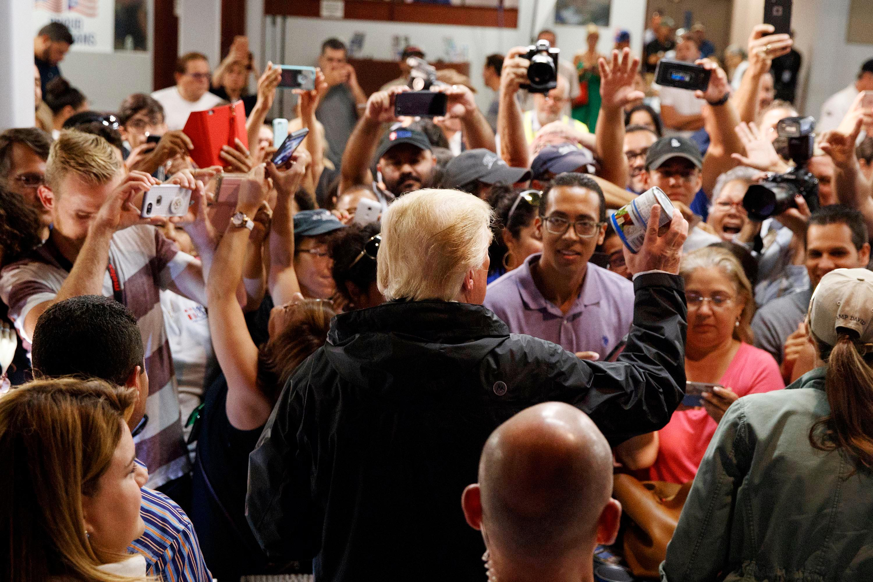 President Donald Trump hands out canned goods and other supplies at Calvary Chapel, Tuesday, Oct. 3, 2017, in Guaynabo, Puerto Rico. Trump is in Puerto Rico to survey hurricane damage. (AP Photo/Evan Vucci)