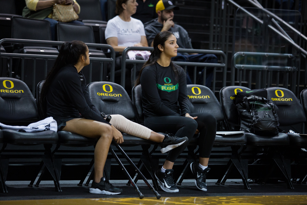 Oregon players Brooke Van Sickle (left) and Jolie Rasmussen (right) sit out tonight's game due to injury. The Oregon volleyball team fell to the the Stanford Cardinal, the defending national champions, in three straight sets Friday night. There were 5,872 people in attendance, the second most at an Oregon volleyball game ever. Photo by Dillon Vibes