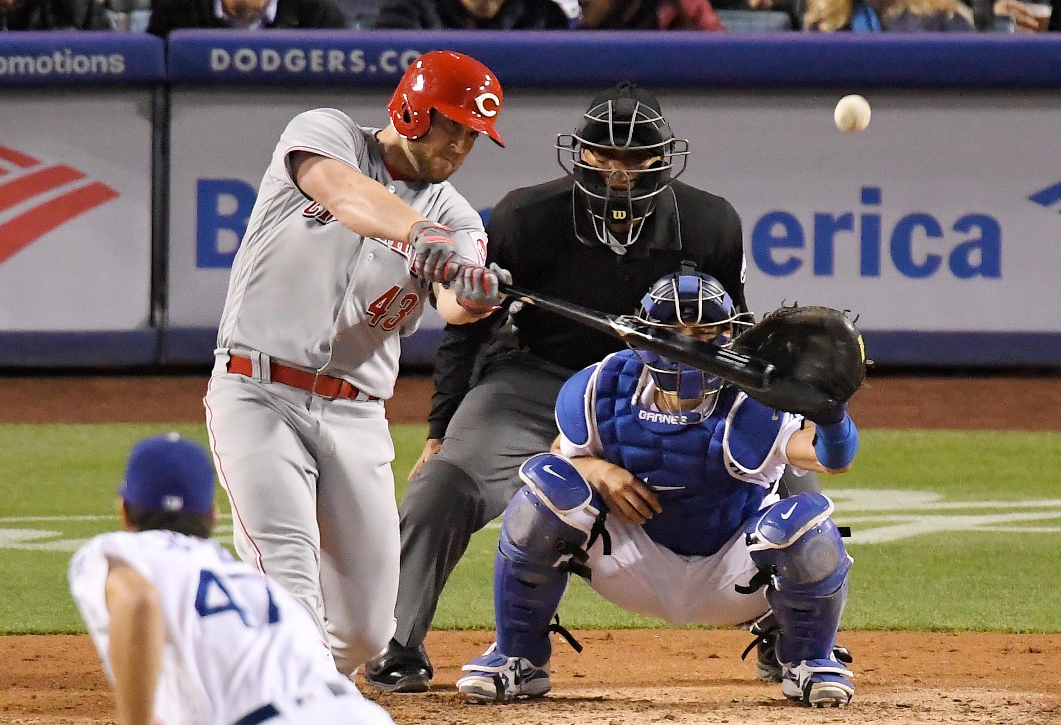 Cincinnati Reds' Scott Schebler hits a three-run home run off Los Angeles Dodgers relief pitcher JT Chargois, front, during the sixth inning of a baseball game Saturday, May 12, 2018, in Los Angeles. (AP Photo/Mark J. Terrill)