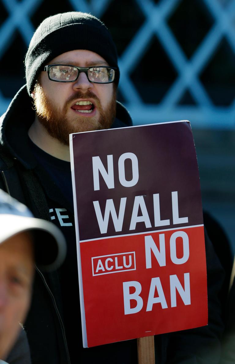 "Eric Buerk, of Seattle, holds a sign that reads ""No Wall No Ban,"" during a protest, Wednesday, Dec. 6, 2017, outside a federal courthouse in Seattle. The U.S. Supreme Court decision allowing President Donald Trump's third travel ban to take effect has intensified the attention on a legal showdown Wednesday before three judges in Seattle who have been cool to the policy as they hear arguments in Hawaii's challenge to the ban, which restricts travel to the United States by residents of six mostly Muslim countries and has been reviled by critics as discriminatory. (AP Photo/Ted S. Warren)"