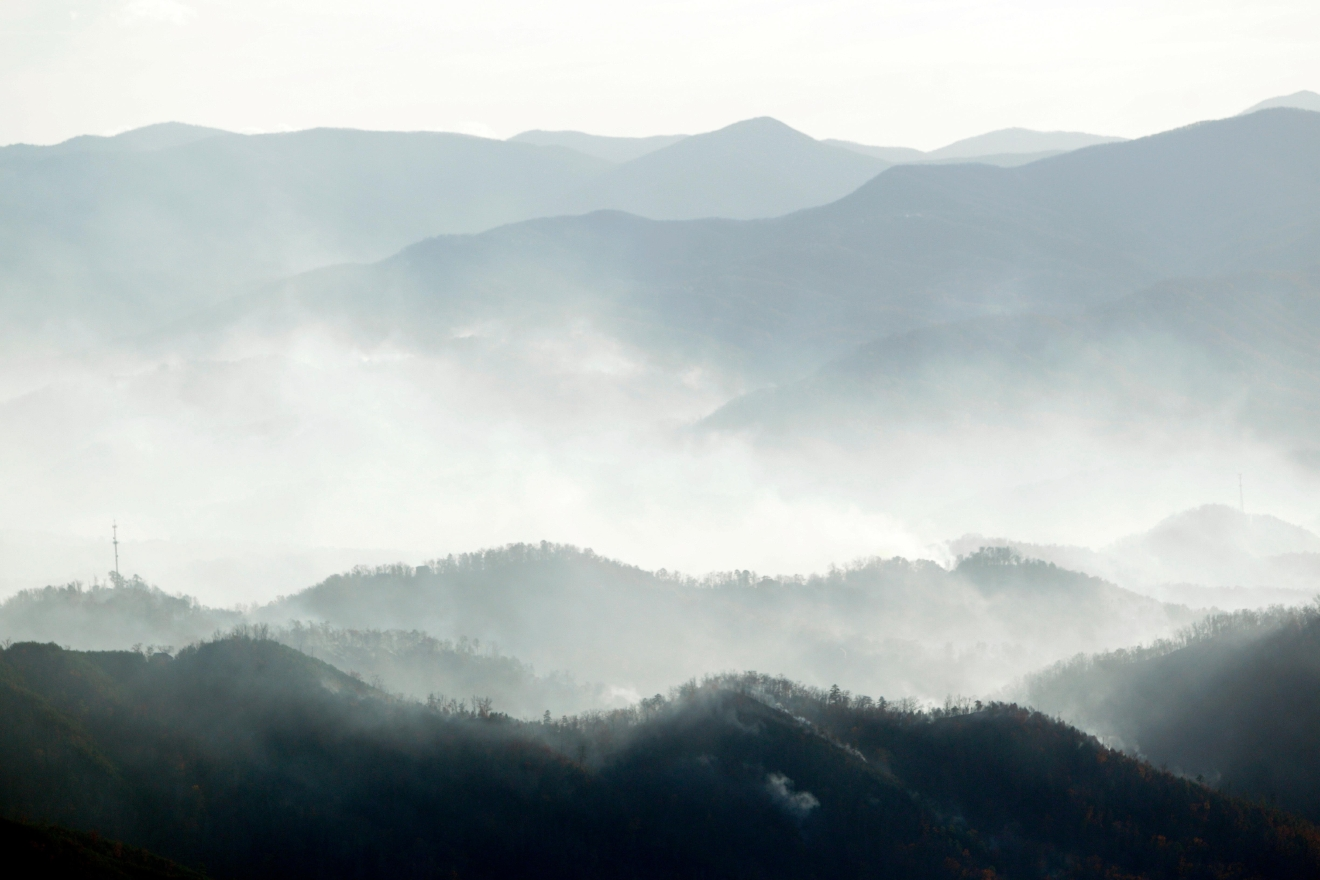 Smoke from wildfires rise above the mountains, Tuesday, Nov. 29, 2016, near Gatlinburg, Tenn. Thousands of people have fled wildfires that killed at least three people and destroyed hundreds of homes and a resort in the Great Smoky Mountains. (AP Photo/Wade Payne)