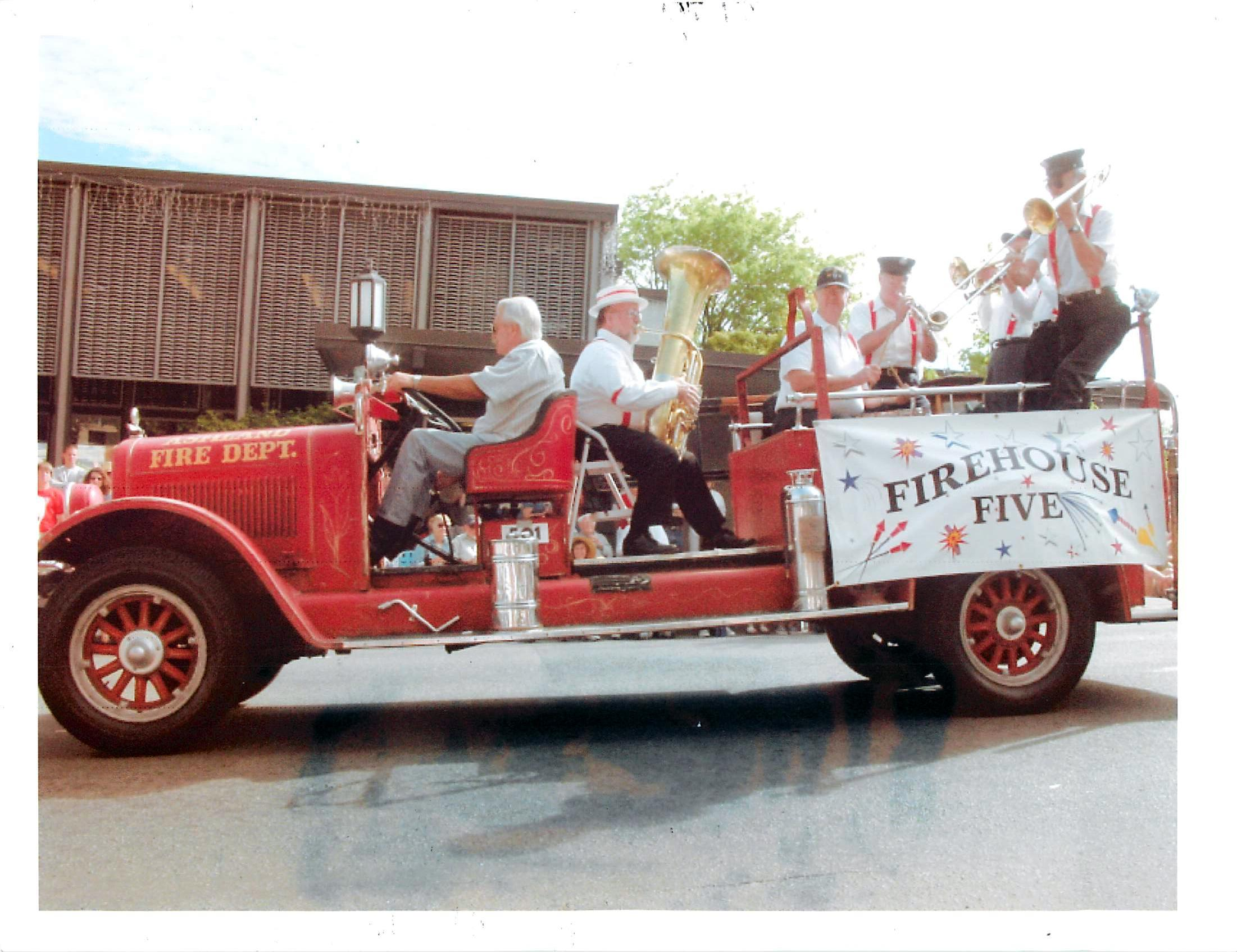 The Firehouse 5 band in the 1926 Reo in the 1989 Ashland 4th of July ParadeJack Tate drives, Mike Knox on tuba, Lyle Ames on drums, Dick Cottle on trumpet and Randy Gugdahl on trombone. Two persons unidentified on the back rail by the hoses. (Photo courtesy of Barbara Knox)