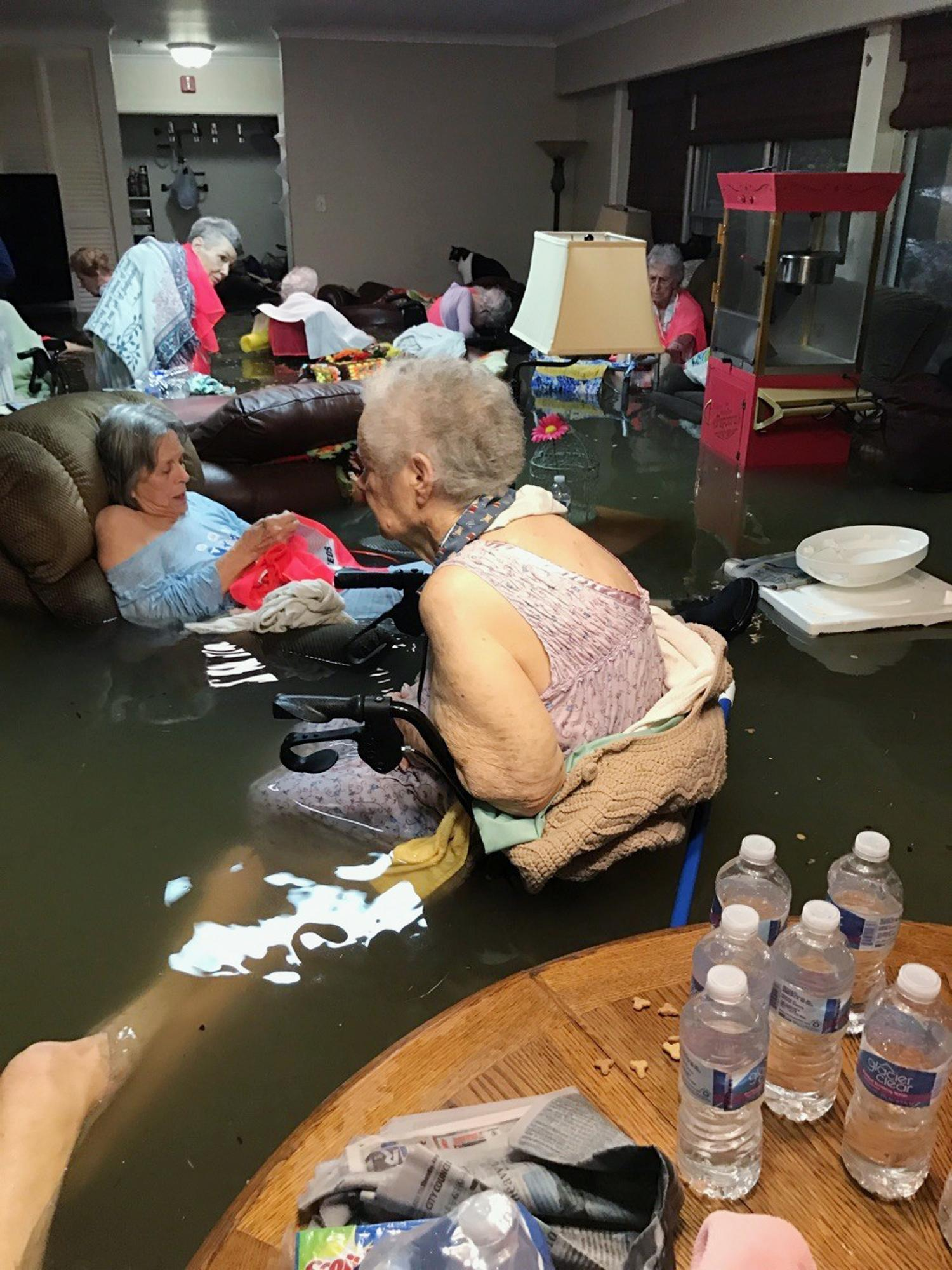 In this Sunday, Aug. 27, 2017, photo provided by Trudy Lampson, residents of the La Vita Bella nursing home in Dickinson, Texas, sit in waist-deep flood waters caused by Hurricane Harvey. Authorities said all the residents were safely evacuated from the facility. (Trudy Lampson via AP)