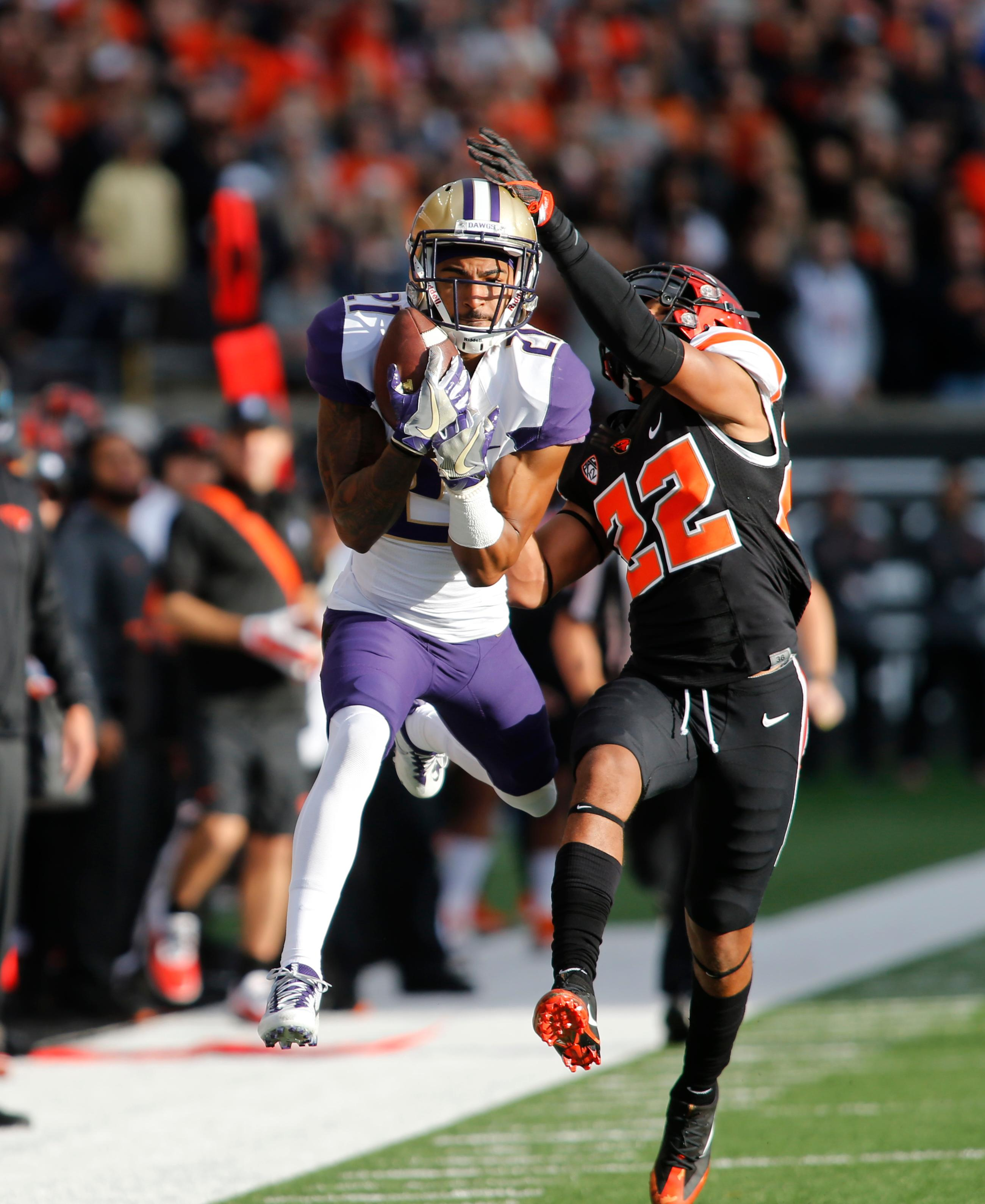 Washington wide receiver Quinten Pounds (21) makes a catch while being defended by Oregon State's Isaiah Dunn in the first half of an NCAA college football game, in Corvallis, Ore., Saturday, Sept. 30, 2017. (AP Photo/Timothy J. Gonzalez)