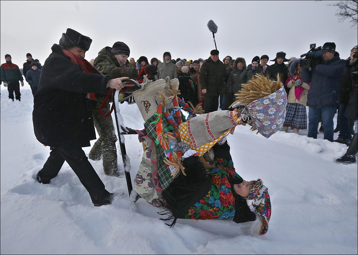 Belarusians wearing national costumes celebrate a Pull the Kolyada Up the Oak rite in the village of Martsiyanauka, some 77 km (48 miles) east of capital Minsk, Belarus, Thursday, Jan. 21, 2016. The merry ancient rite Pull the Kolyada Up the Oak marks the end of Orthodox Christmas celebrations in Belarus. On Jan. 21 a wheel, the so-called Kolyada, would be pulled up an oak or any old tree. The Belarusians believed that the ritual heralds a good harvest, luck and happiness for the entire year. (AP Photo/Sergei Grits)