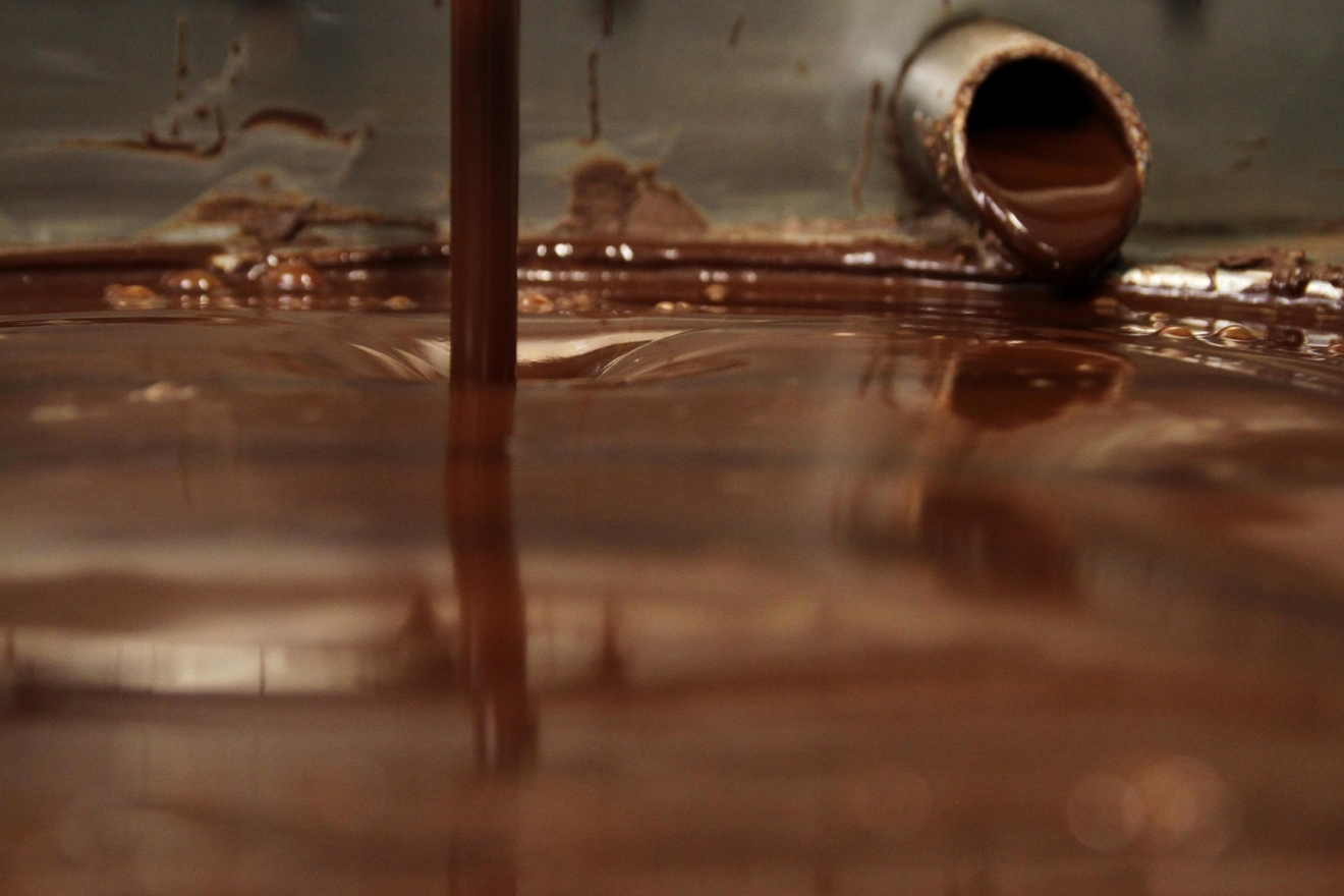The chocolate is broken down and heated up in a tempering machine, which continually mixes the liquid until it's smooth.  (Image: Amanda Andrade-Rhoades/ DC Refined)