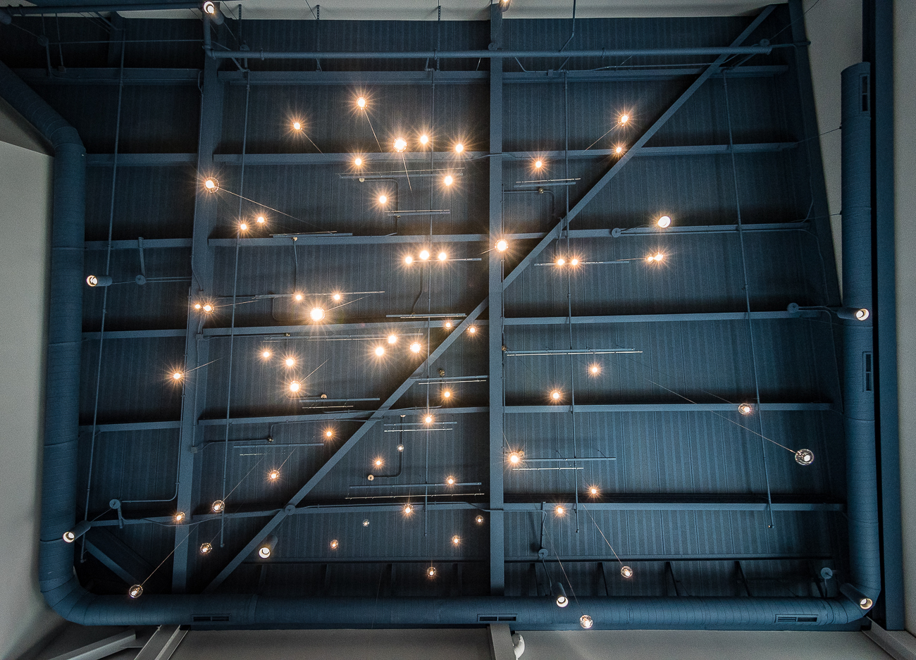 The arrangement of lights above the lobby's 2-story atrium represents being outdoors beneath a darkened sky pin-pricked with starlight. / Image: Phil Armstrong, Cincinnati Refined // Published: 9.7.17