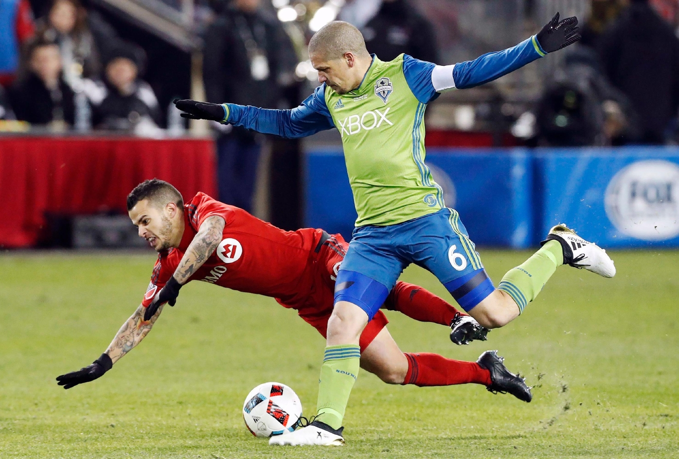 Seattle Sounders midfielder Osvaldo Alonso (6) tackles Toronto FC forward Sebastian Giovinco, left, during second-half MLS Cup final soccer action in Toronto, Saturday, Dec. 10, 2016. (Mark Blinch/The Canadian Press via AP)