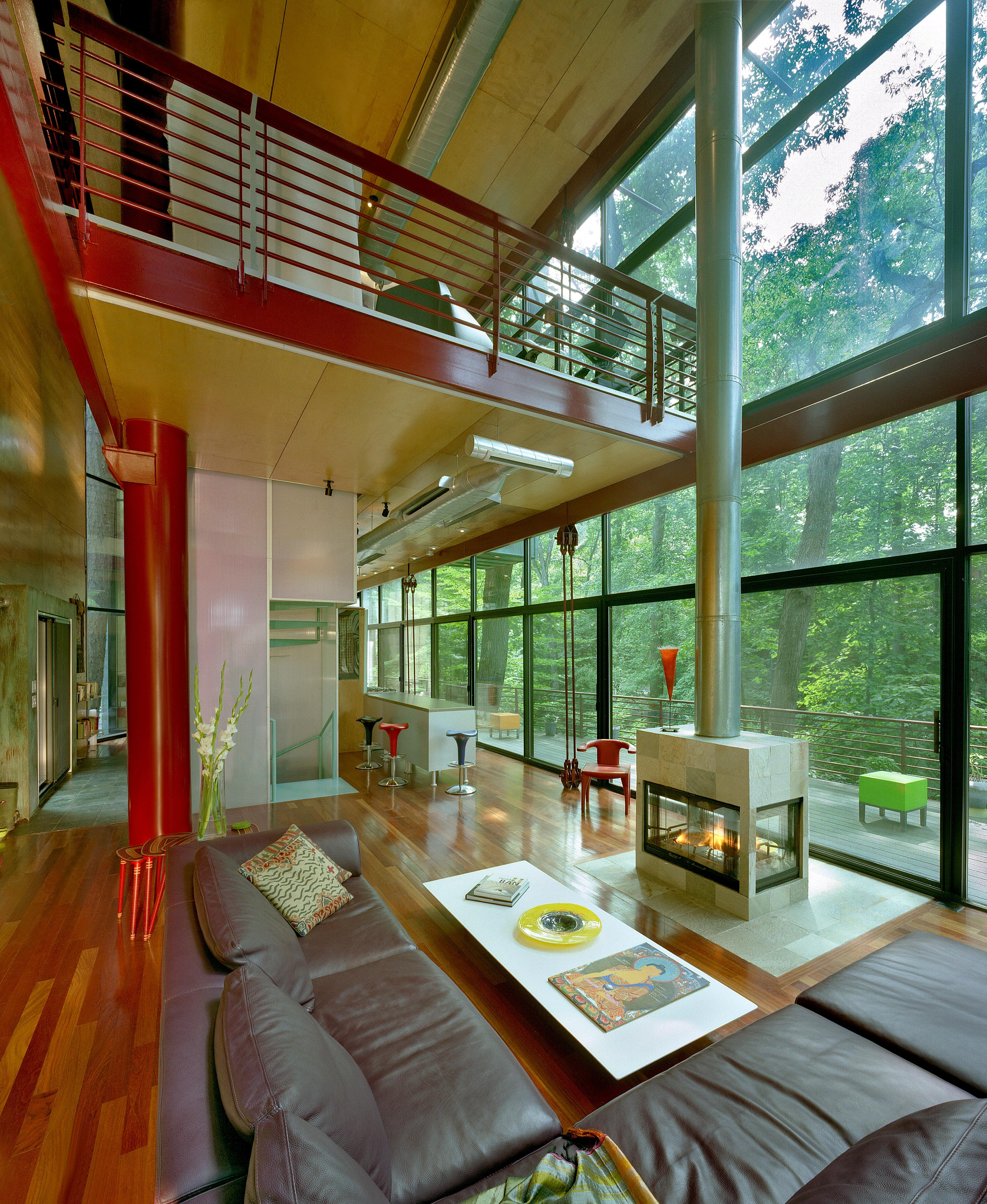 The home is inspired by the simple and natural virtues of the site's trees and rock outcroppings. An abundance of trees splitting rocks near a stream bed are the essences of the Park running through the center of D.C. The home is seen as an abstracted tree with a street side of patina copper planted on two columns at the cliff's edge hung by steel cables. The park side rear is clad with transparent super-insulated glazing. Trees are saved and wrap through the house. The design desires to blend into the park by its matching natural colors as well as its use of glass which reflectively display the preserved trees surrounding it. (Image: Ken Wyner)
