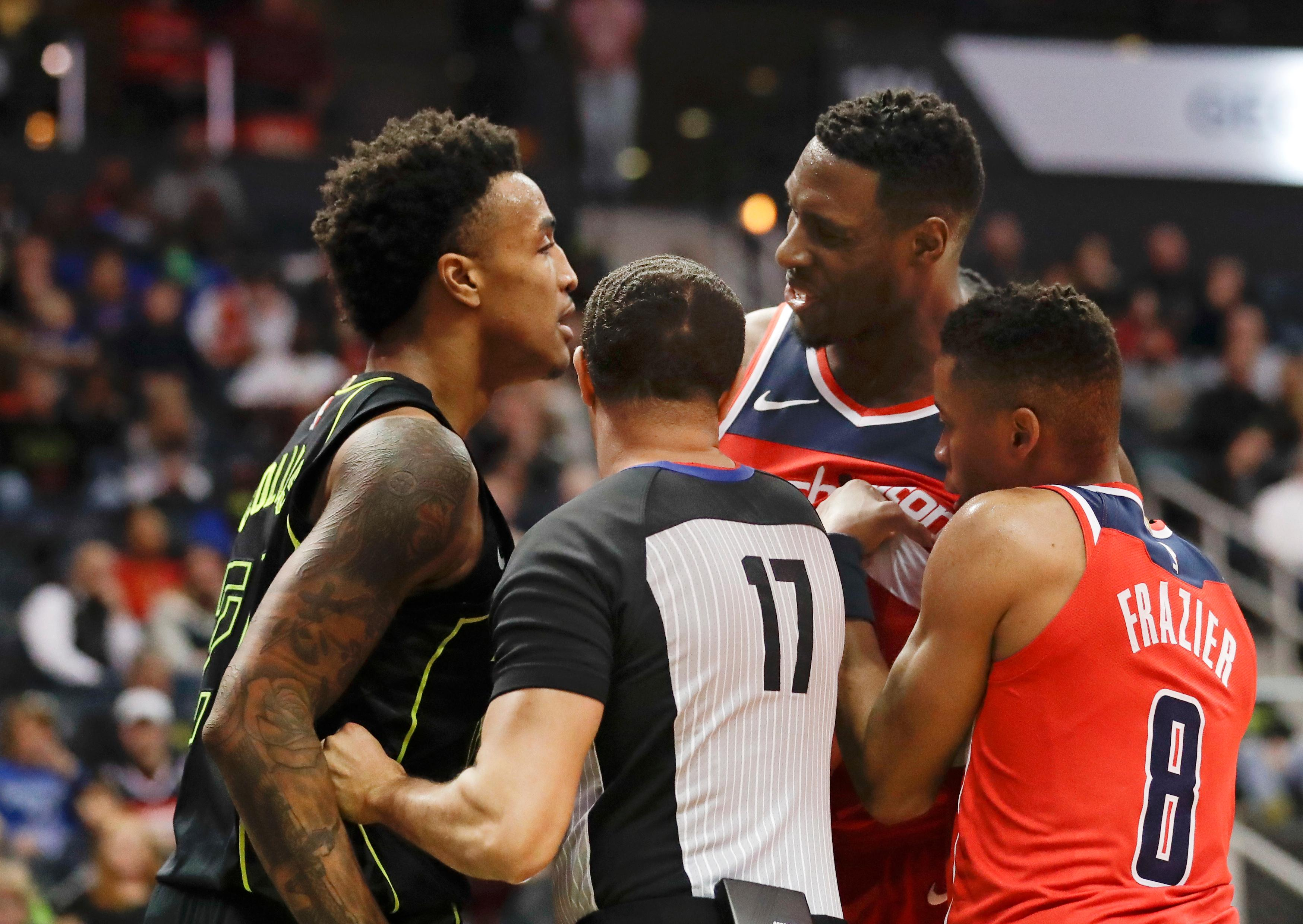 An official steps between Atlanta Hawks forward John Collins (20) and Washington Wizards center Ian Mahinmi (28) as tempers flare during the first half of an NBA basketball game Saturday, Jan. 27, 2018, in Atlanta. (AP Photo/John Bazemore)