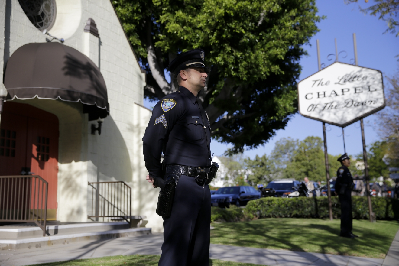 A police officer stands guard outside a mortuary where a small ceremony for former first lady Nancy Reagan will take place, Wednesday, March 9, 2016, in Santa Monica, Calif. Three days of formal mourning and solemn ceremonies for former first lady Nancy Reagan are set to begin Wednesday. (AP Photo/Jae C. Hong)