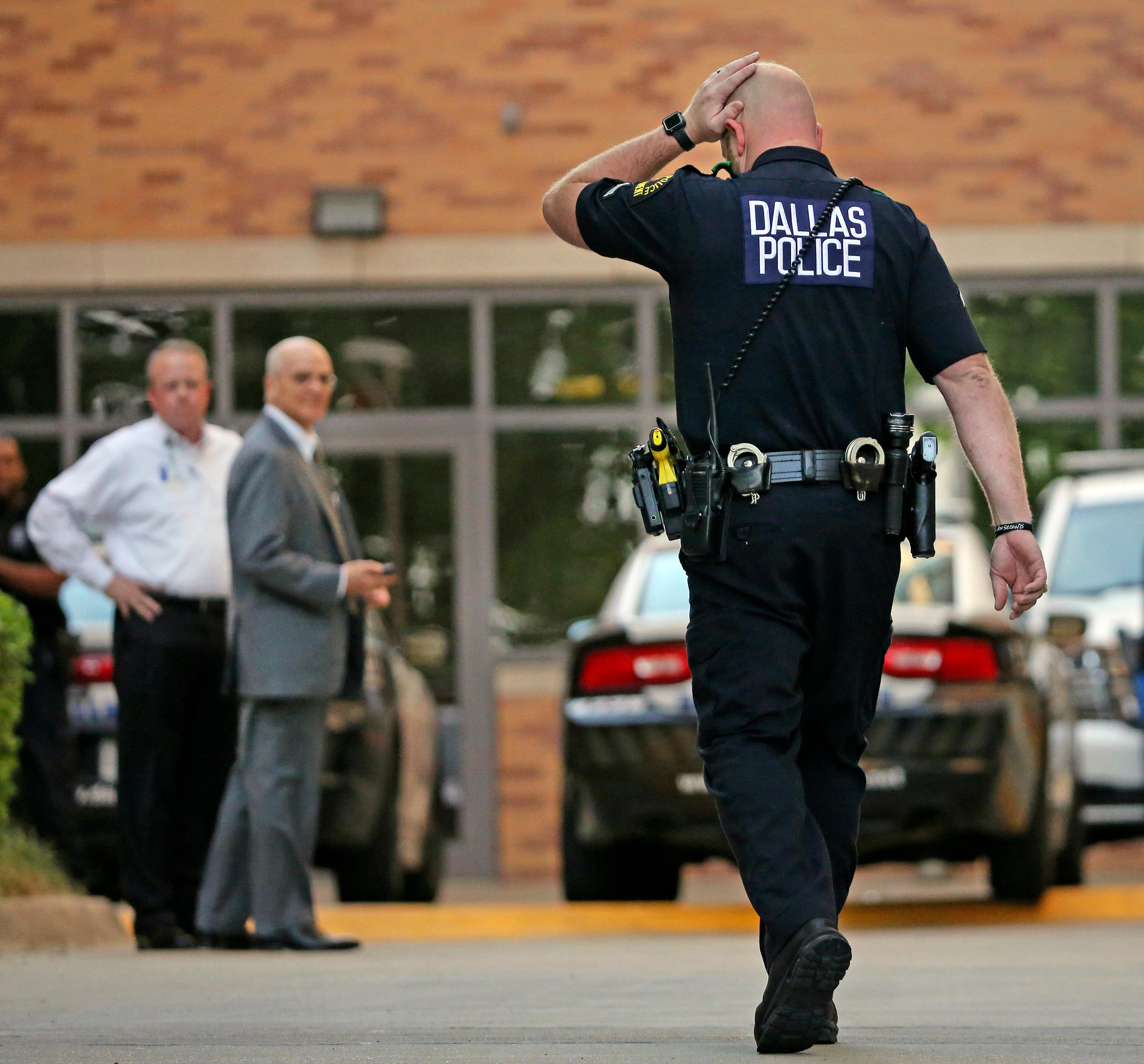 A Dallas Police officer walks to the entrance of the emergency room at Presbyterian Hospital, Tuesday, April 24, 2018, in Dallas, following a shooting at an area Home Depot where two police officers and a civilian were shot. The officers were critically wounded in the shooting, according to officials. (Louis DeLuca/The Dallas Morning News via AP)