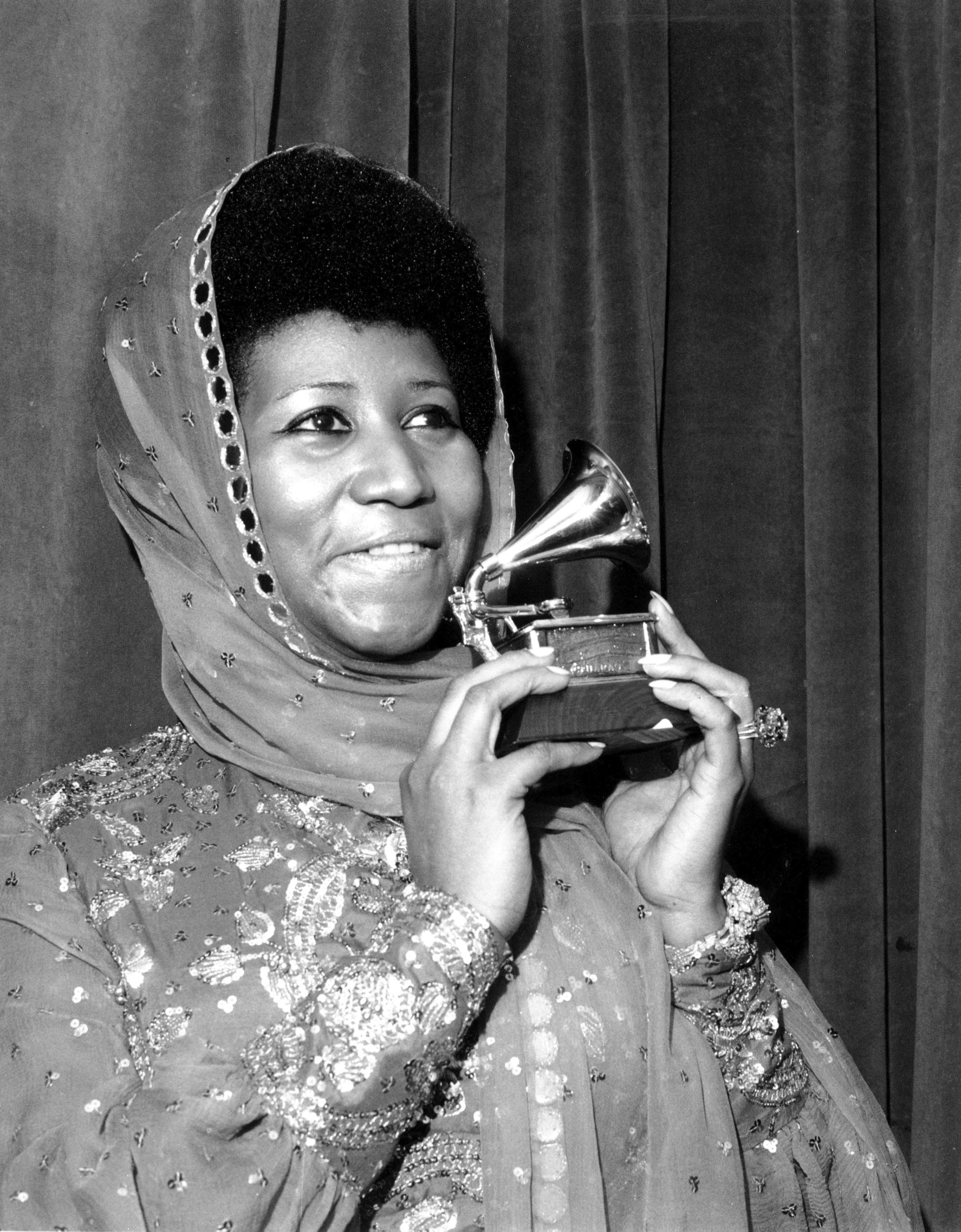 "FILE - In this March 3, 1975 file photo, singer Aretha Franklin poses with her Grammy Award for for best female R&B vocal performance for ""Ain't Nothing Like the Real Thing"" at the 17th Annual Grammy Award presentation in New York.   Franklin died Thursday, Aug. 16, 2018 at her home in Detroit.  She was 76. (AP Photo, File)"