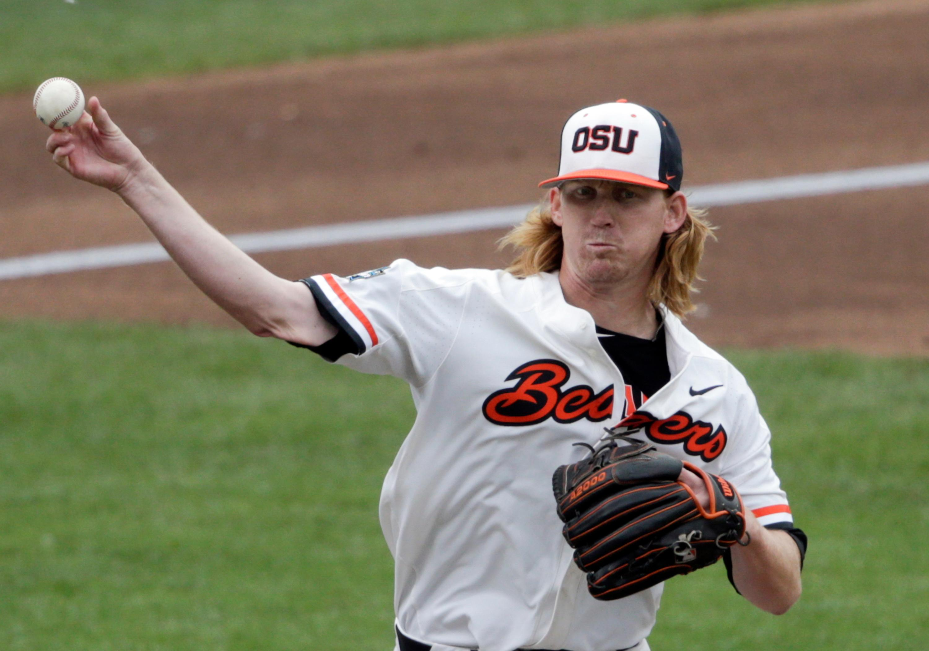 Oregon State pitcher Bryce Fehmel throws to first on a pickoff-attempt in the first inning of an NCAA College World Series baseball game against Mississippi State in Omaha, Neb., Friday, June 22, 2018. (AP Photo/Nati Harnik)