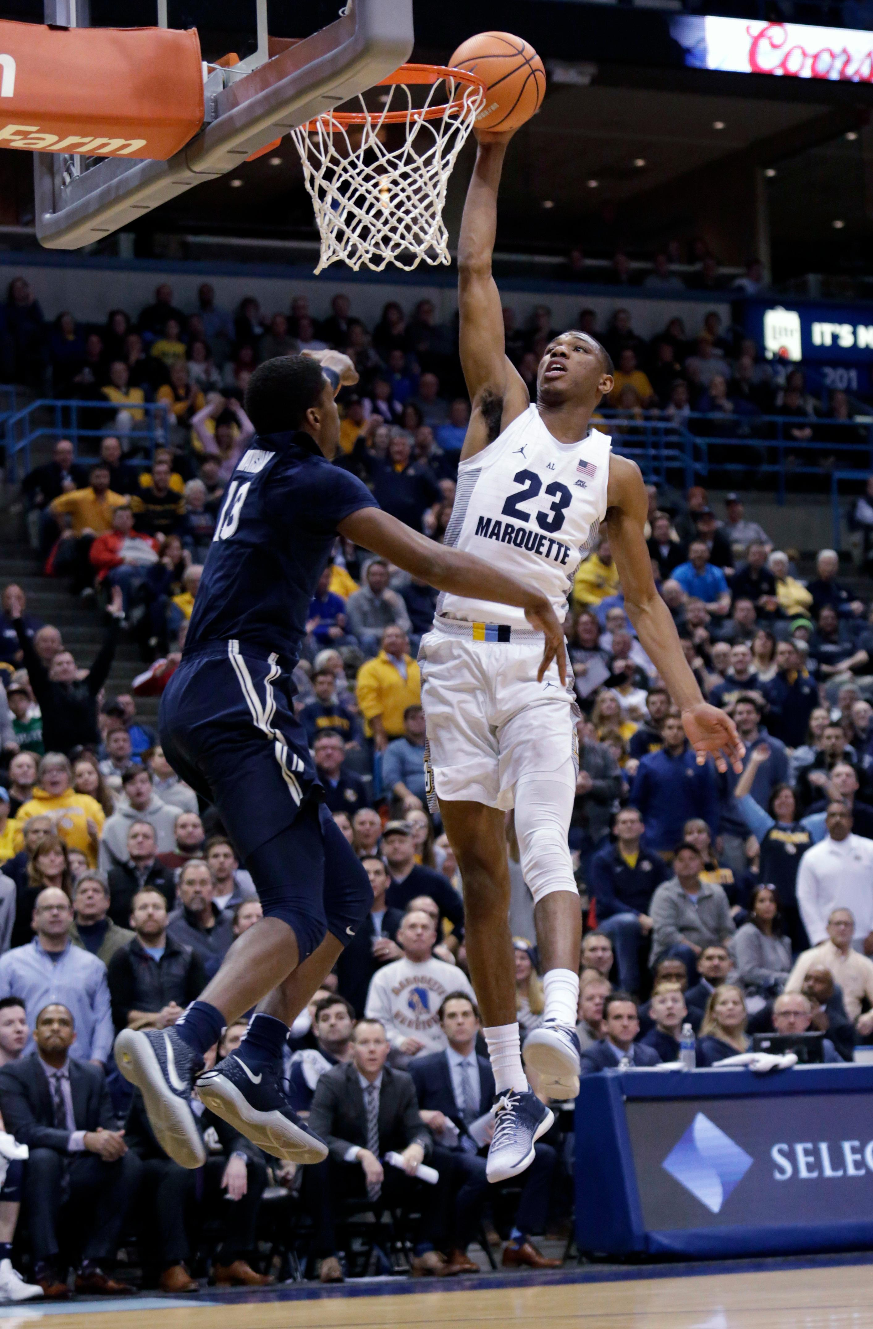 Marquette forward Jamal Cain, right, goes up for a basket agains the defense of Xavier forward Naji Marshall, left, during the first half of a basketball game, Wednesday, Dec. 27, 2017, in Milwaukee. (AP Photo/Darren Hauck)