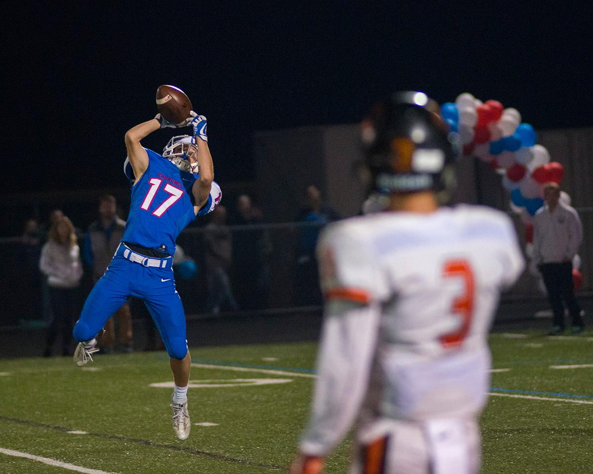 Churchill Lancers Stuart Helikson (#17) makes the catch to complete the pass. Churchill defeated Crater 63-21 on Friday at their homecoming game. Churchill remains undefeated with a conference record of 9-0. Photo by Rhianna Gelhart, Oregon News Lab