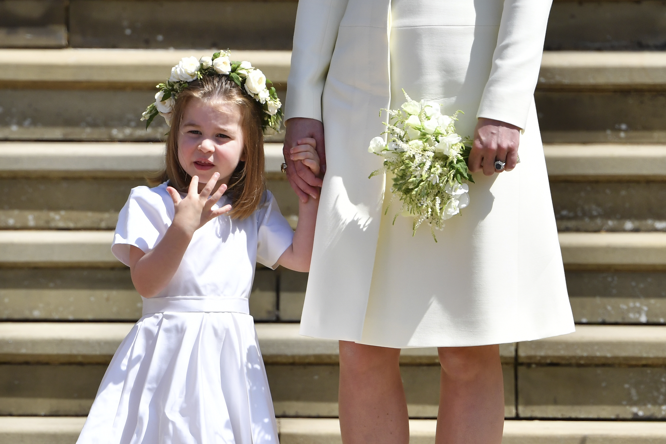 Britain's Princess Charlotte holds the hand of her mother Kate, Duchess of Cambridge after the wedding ceremony of Prince Harry and Meghan Markle at St. George's Chapel in Windsor Castle in Windsor, near London, England, Saturday, May 19, 2018. (Ben Stansall/pool photo via AP)