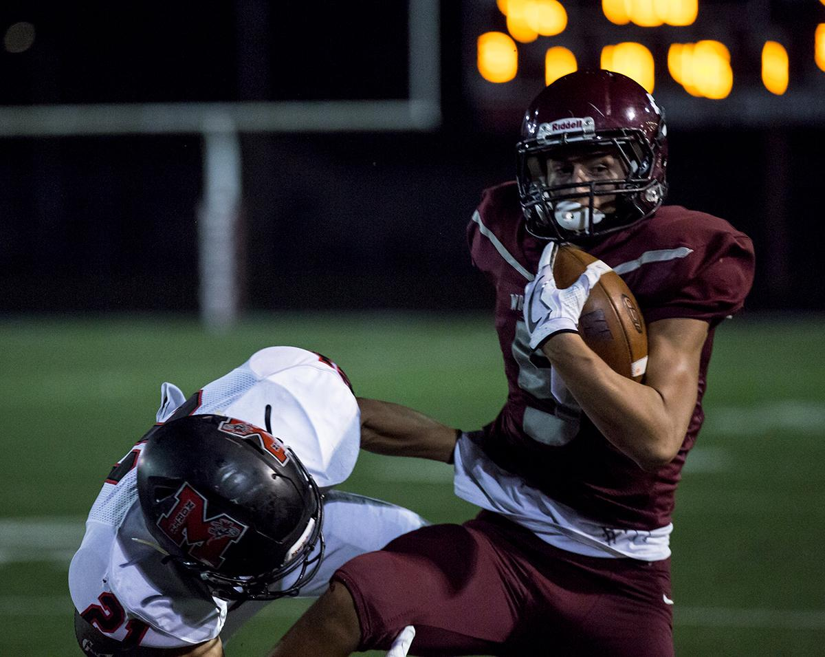 Willamette's Tanner Branson (#5) is brought down by North Medford's Tyler Evans (#21). The North Medford Black Tornado defeated the Willamette Wolverines 45 – 19 on Friday, October 27, at Willamette High School, concluding the season for both teams. Photo by Kit MacAvoy, Oregon News Lab