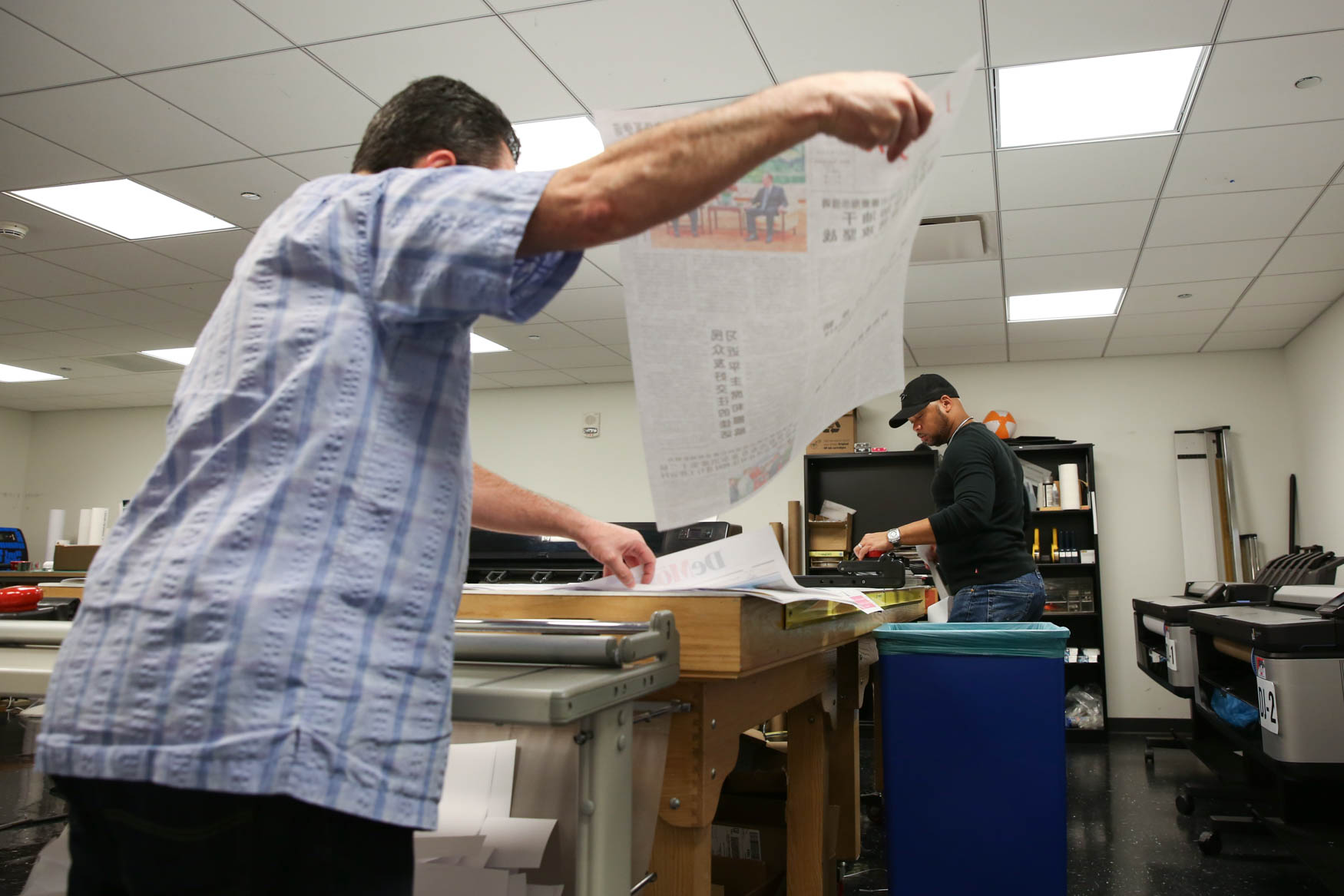Mike Machado, left, and graphics specialist Frank Mitchell, retrieve the newspapers from the printer and then cut off the excess paper.{ }(Amanda Andrade-Rhoades/DC Refined)