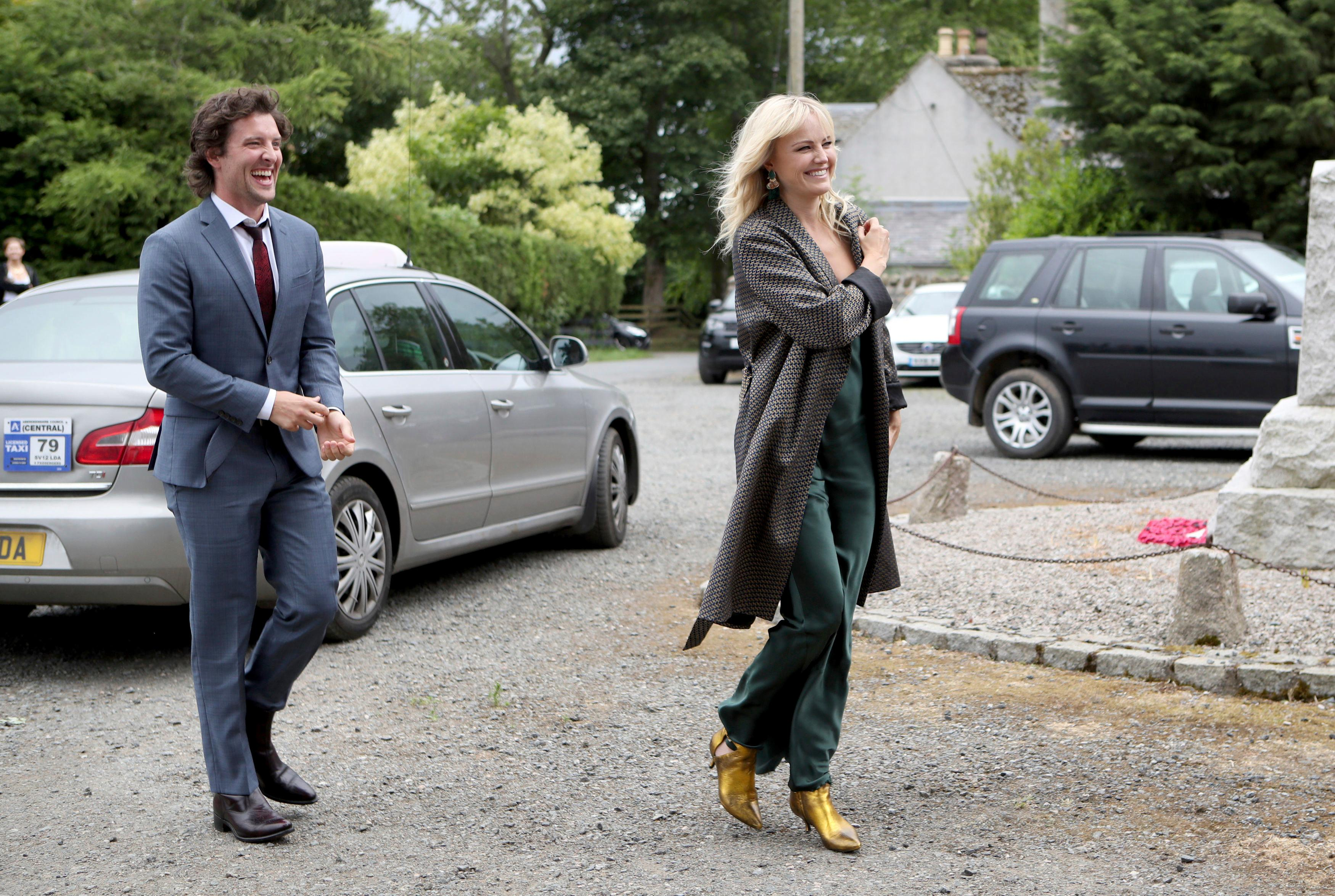 "Actor Jack Donnelly arrives with partner Malin Akerman for the wedding ceremony of Game Of Thrones actors Kit Harington and Rose Leslie, at Rayne Church, Kirkton of Rayne in Aberdeenshire, Scotland, Saturday June 23, 2018. Former ""Game of Thrones"" co-stars Kit Harington and Rose Leslie are marrying Saturday with a celebration at the bride's family castle in Scotland. The couple and guests arrived at Rayne Church, close to the 900-year-old Wardhill Castle in northeast Scotland, which is owned by Leslie's family. (Jane Barlow/PA via AP)"