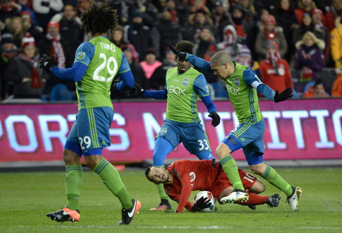 Seattle Sounders midfielder Osvaldo Alonso, right, trips Toronto FC forward Sebastian Giovinco as Sounders defender Roman Torres, left, and Joevin Jones, center, look on during first-half MLS Cup final soccer action in Toronto, Saturday, Dec. 10, 2016. (Nathan Denette/The Canadian Press via AP)